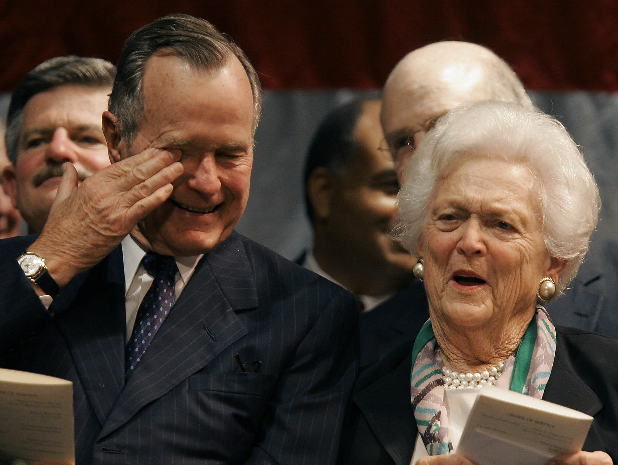 "Former President George H. W. Bush wipes his eyes as he and his wife, Barbara Bush, laugh during one of the eulogies praising longtime family friend and former Rep. G.V. ""Sonny"" Montgomery, a Mississippi Democrat, at the Temple Theater in Meridian, Miss., Tuesday, May 16, 2006, during Montgomery's public funeral."