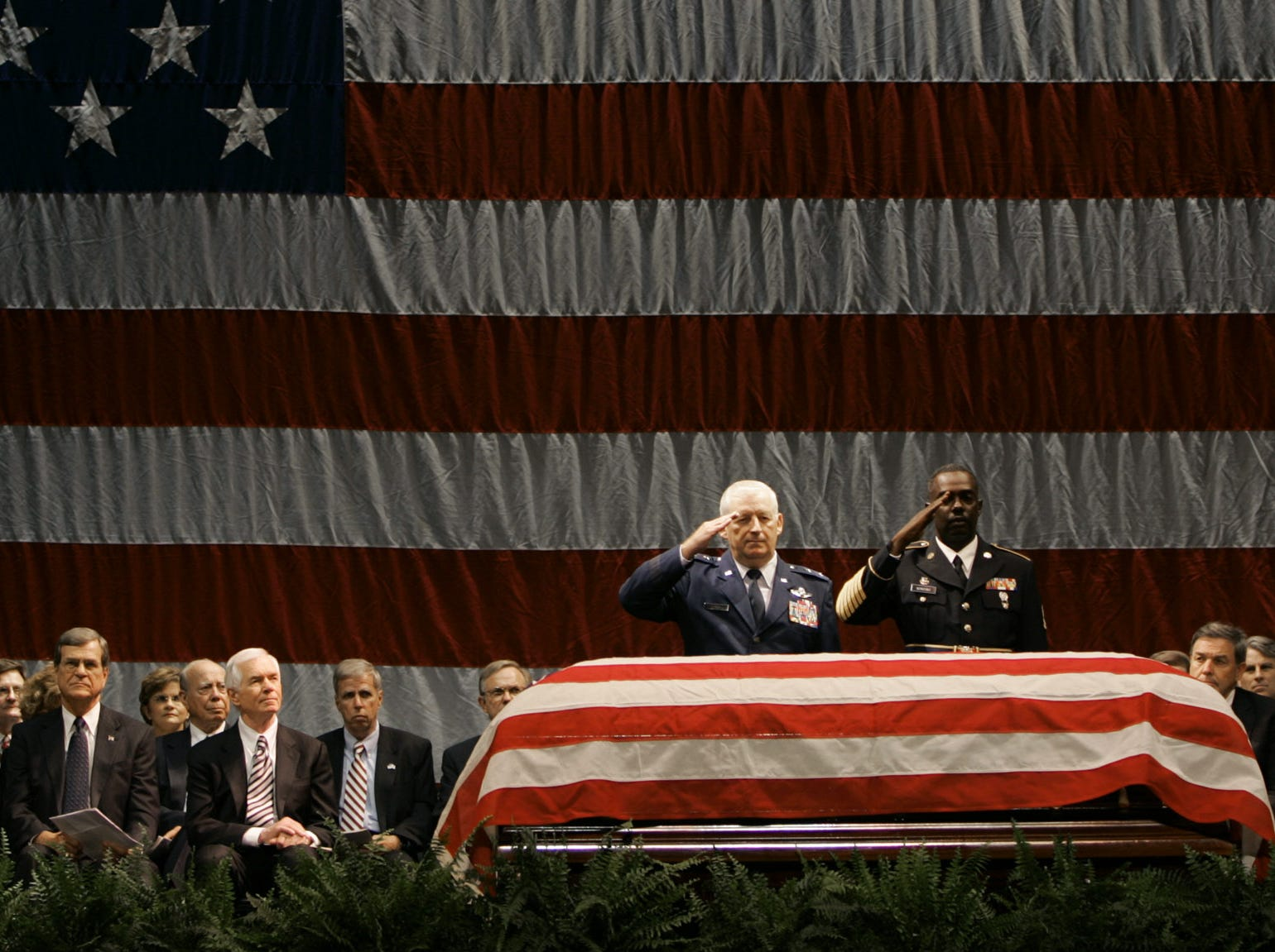 "A large number of dignitaries sat at center stage as Mississippi Adjutant General, Major Gen. Harold Cross, second from right, and an unidentified soldier salute the casket bearing the body of former U.S. Rep. G.V. ""Sonny"" Montgomery, D-Miss., during a public funeral. Among the dignitaries were, from left, former President George H. W. Bush; his wife Barbara Bush; U.S. Sen. Trent Lott, R-Miss.; U.S. Sen. Thad Cochran, R-Miss."