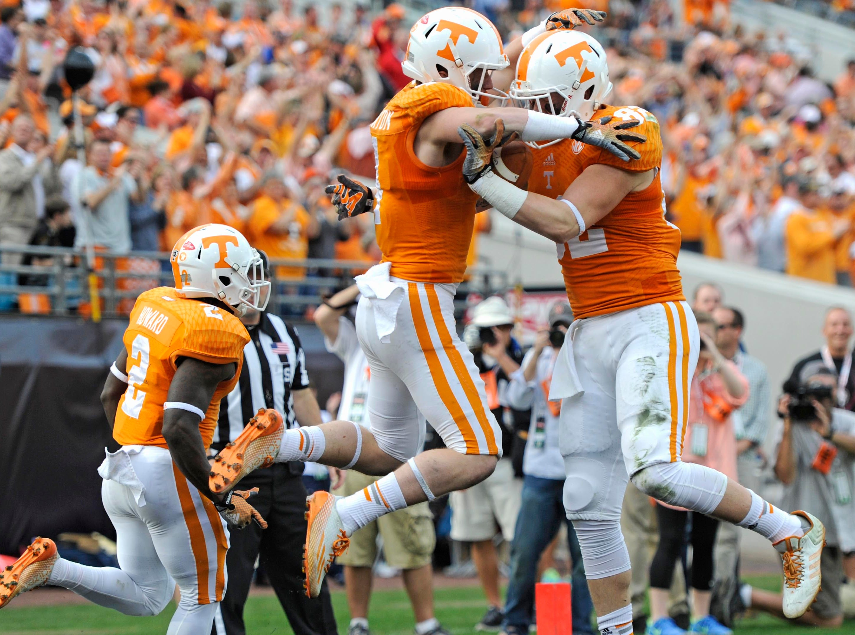 Tennessee wide receiver Vic Wharton (4), center, and Tennessee tight end Ethan Wolf (82), right, celebrate after Wharton scored a touchdown against Iowa during the first half of the TaxSlayer Bowl at EverBank Field on Friday, Jan. 2, 2015 in Jacksonville, Fla.