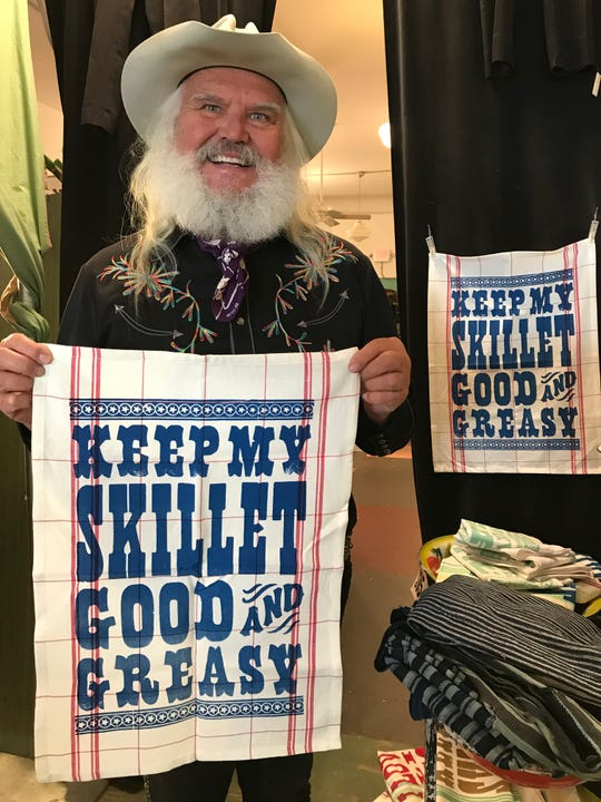 A locally printed towel for your country cook is $15 at Pioneer House, shown off here by store co-owner Cowboy Phil.
