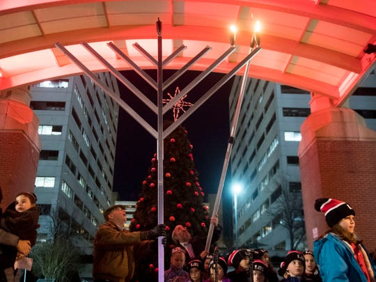 Rabbi Yossi Wilhelm lights the second candle of the menorah during Knoxville's first Chanukah in the City at Market Square on Monday, December 3, 2018.