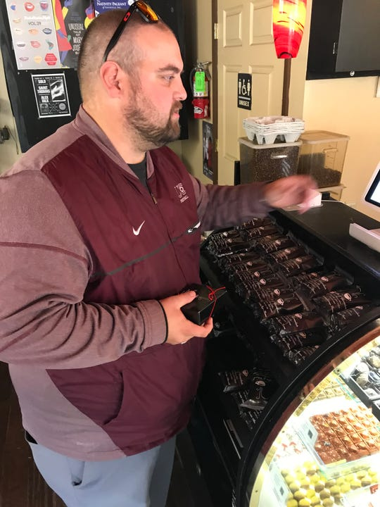 Zack Santolla of Charleston, W.Va., picks up a gift at Coffee & Chocolate on Union Avenue. Santolla's wife, who went to UT, asked him to pick up tiramisu and Jack Daniel's flavored truffles on his way through Knoxville.