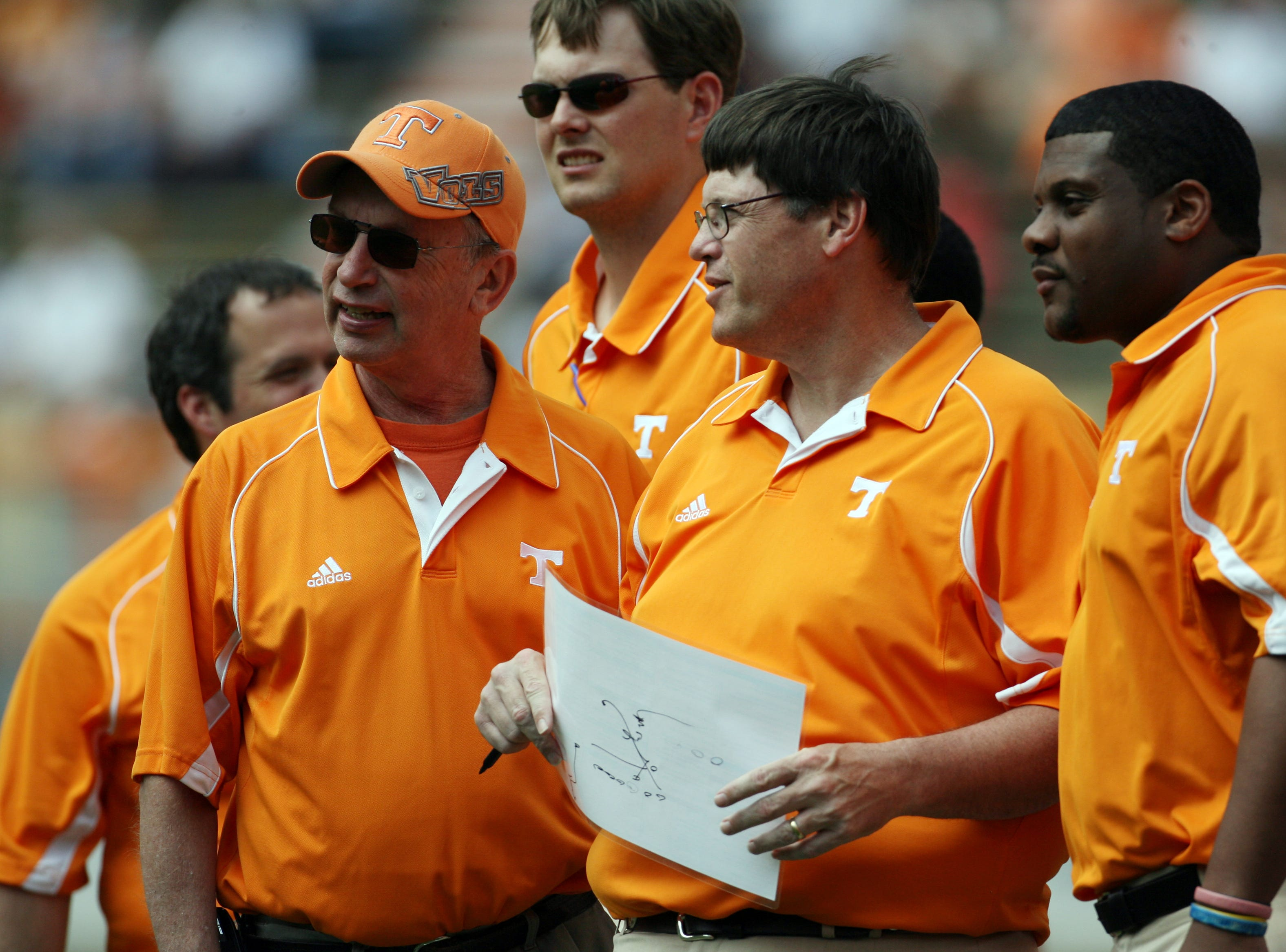 News Sentinel sports writer and celebrity head coach John Adams, left, chats with Tennessee assistant coach Jim Chaney, center, during the Orange and White game at Neyland Stadium Saturday, Apr. 17, 2010.