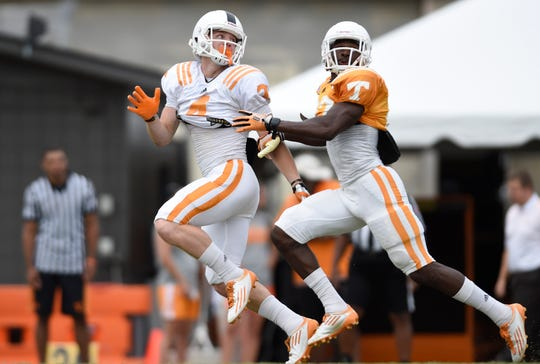 Tennessee wide receiver Vic Wharton (4), left, looks for a pass as defensive back Justin Coleman (27), right, defends during football practice at Haslam Field in Knoxville on Friday, Aug. 8, 2014.
