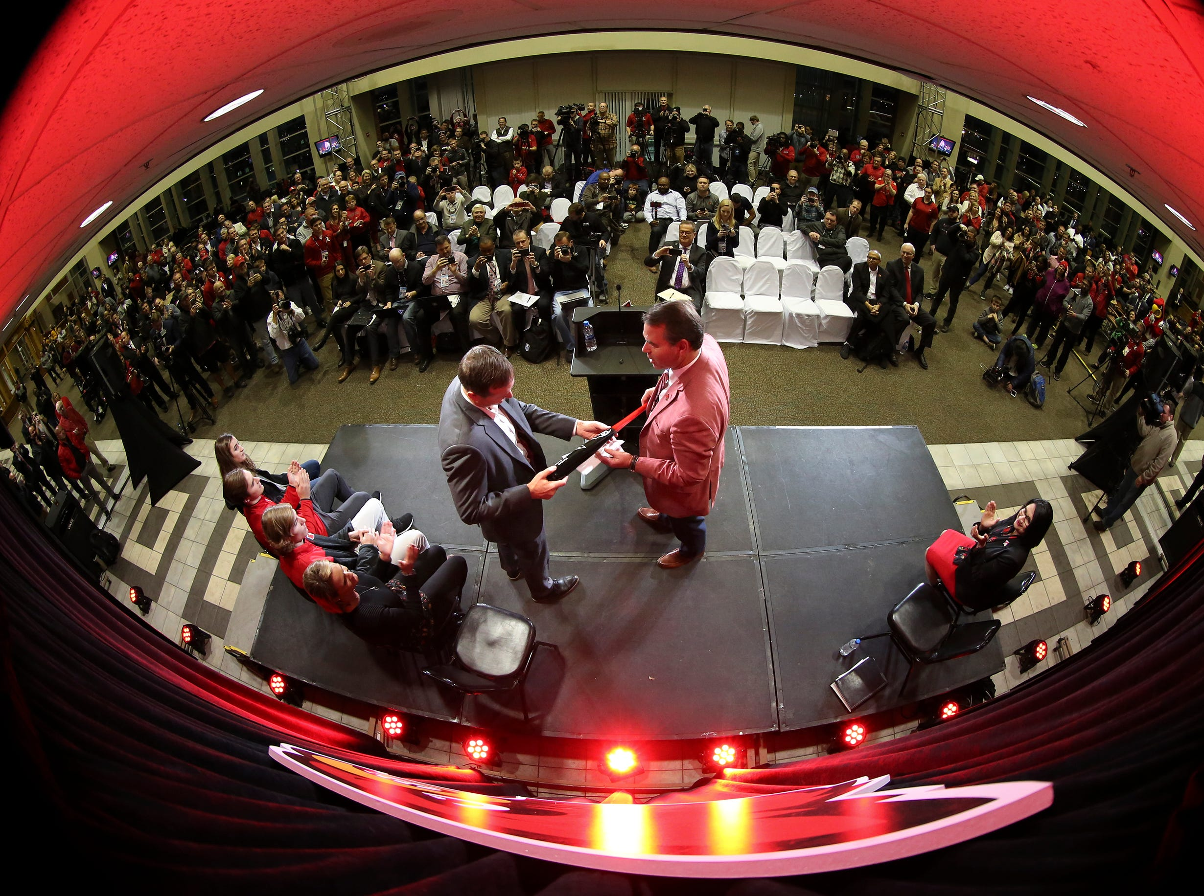 Coach Scott Satterfield receives a Louisville Slugger from UofL Athletic Director Vince Tyra as Satterfield is named the new head coach at Louisville on Tuesday evening.December 4, 2018
