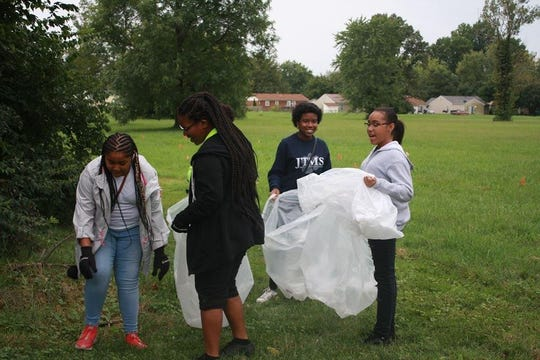 Students in Louisville's Black Achievers Program worked to clean up the grounds at the Newburg library, community center and park.