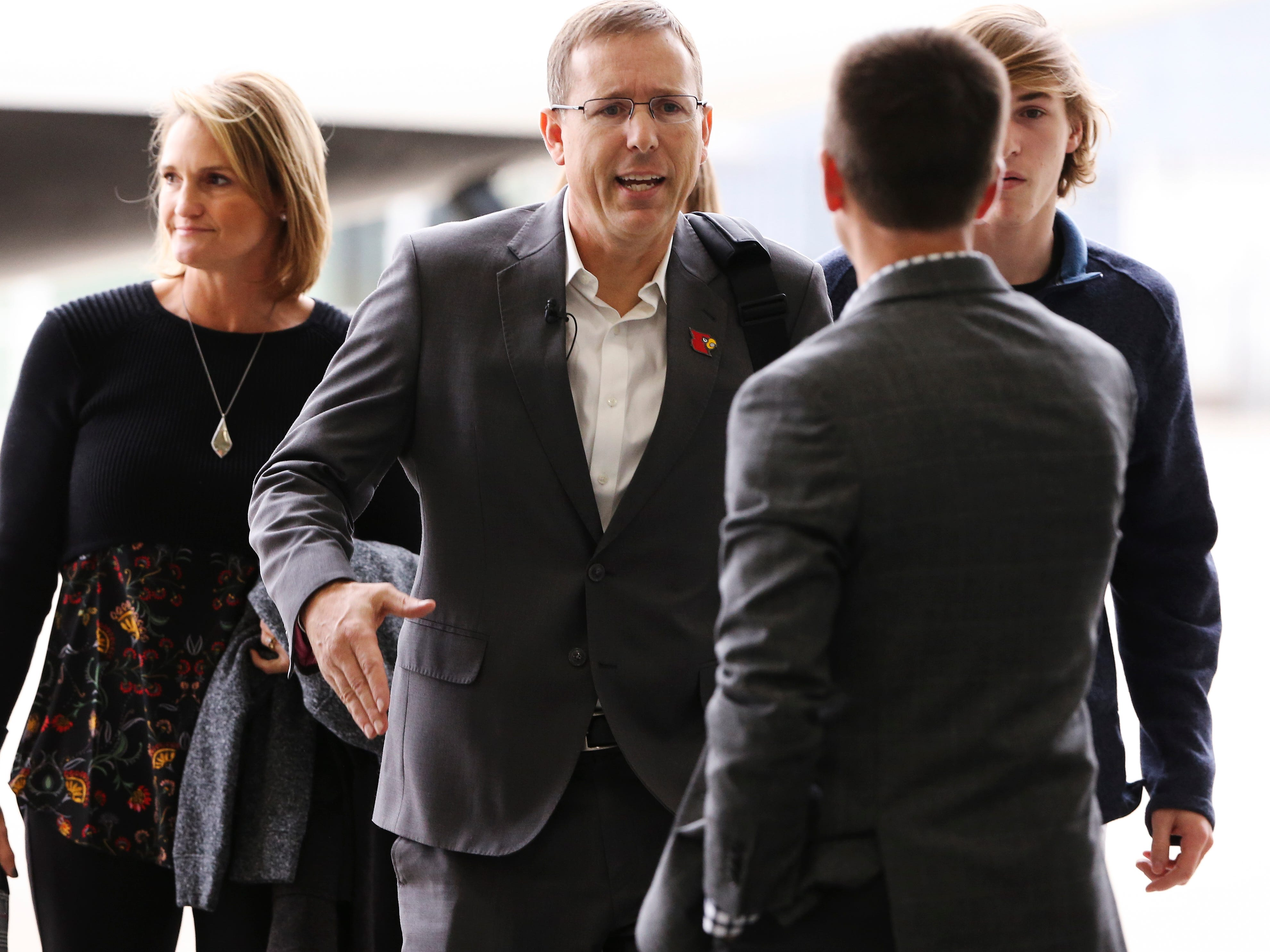 Appalachian State head football coach Scott Satterfield, center, greets people after exiting a private plane with his family in Louisville where he expects to be named the new head football coach at U of L.  