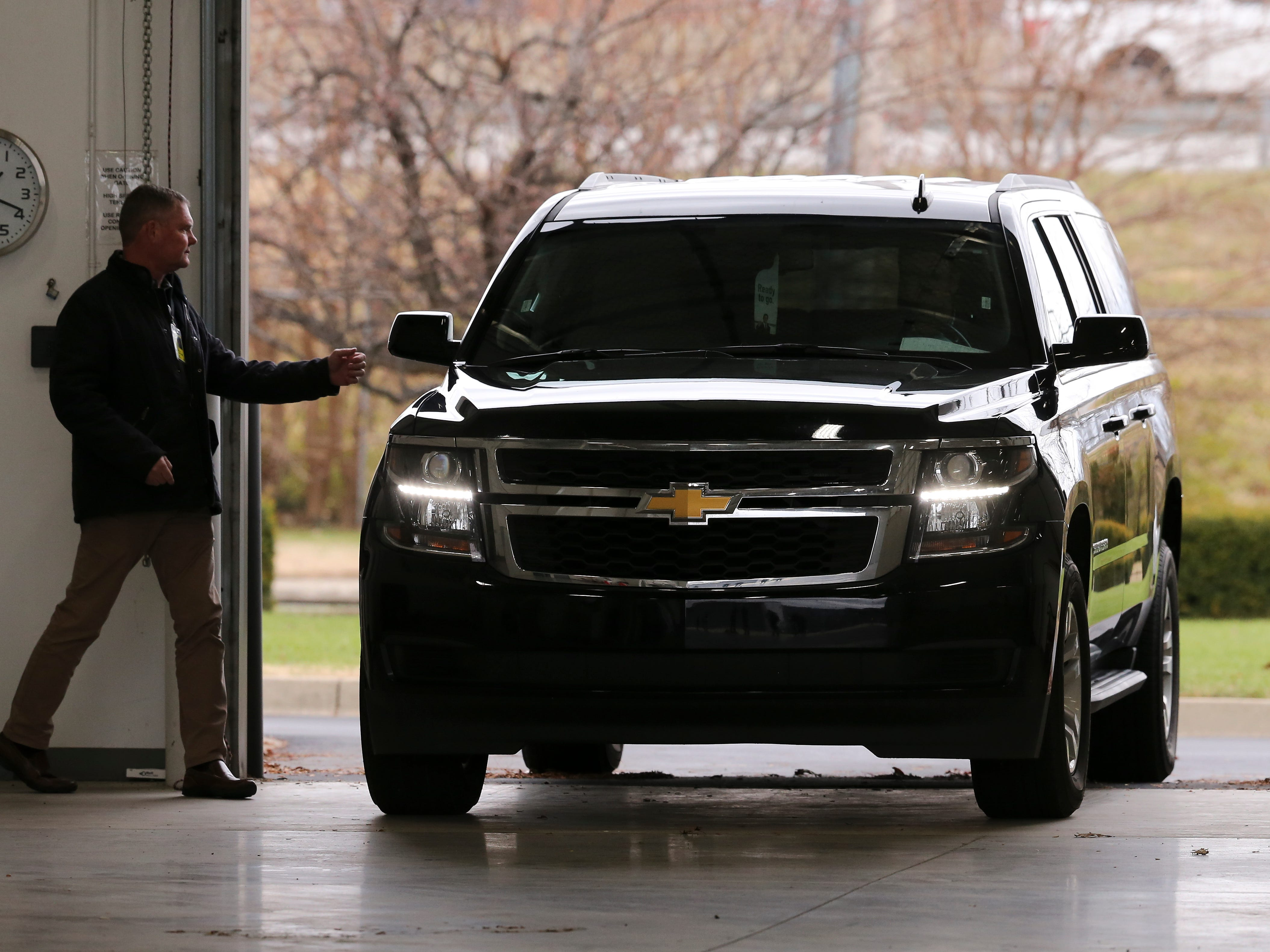 A technician opens a garage door to let an SUV into a hangar to pick up Appalachian State head football coach Scott Satterfield following his arrival in Louisville.  Satterfield expects to be named the new head football coach at U of L.  Dec. 4, 2018
