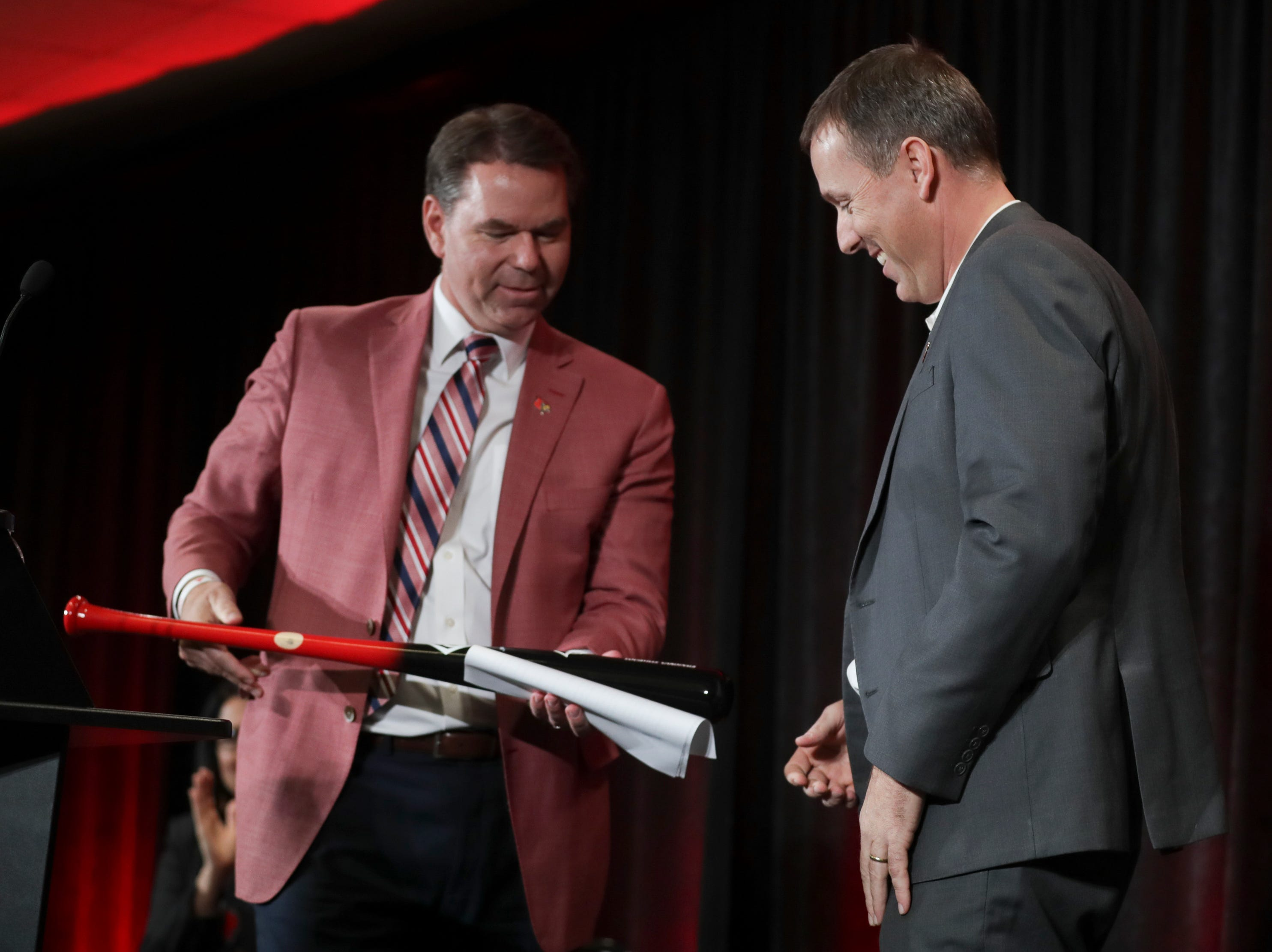 Coach Scott Satterfield receives a Louisville Slugger from UofL Athletic Director Vince Tyra as Satterfield is named the new head coach at Louisville on Tuesday evening.