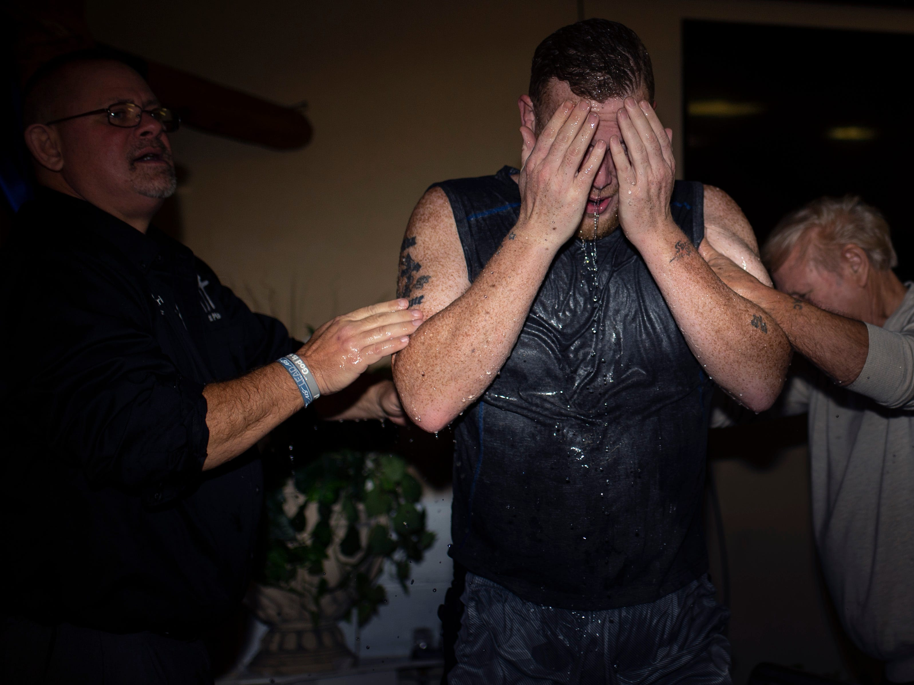 "Pastor and founder Kris Hunley, left, looks on as Bobby Sizemore emerges from the water after his baptism at Todd's Place Transitional Housing in Seymour, Indiana. ""If the guys like me that helped tear up Austin will go back and change their life and help put it back together, we'll have it fixed in no time,"" Hunley said. Dec. 2, 2018"