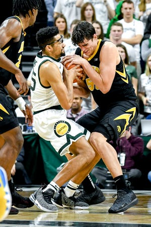 Michigan State's Kenny Goins, left, and Iowa's Luka Garza battle for control of the ball during the first half on Monday, Dec. 3, 2018, at the Breslin Center in East Lansing.