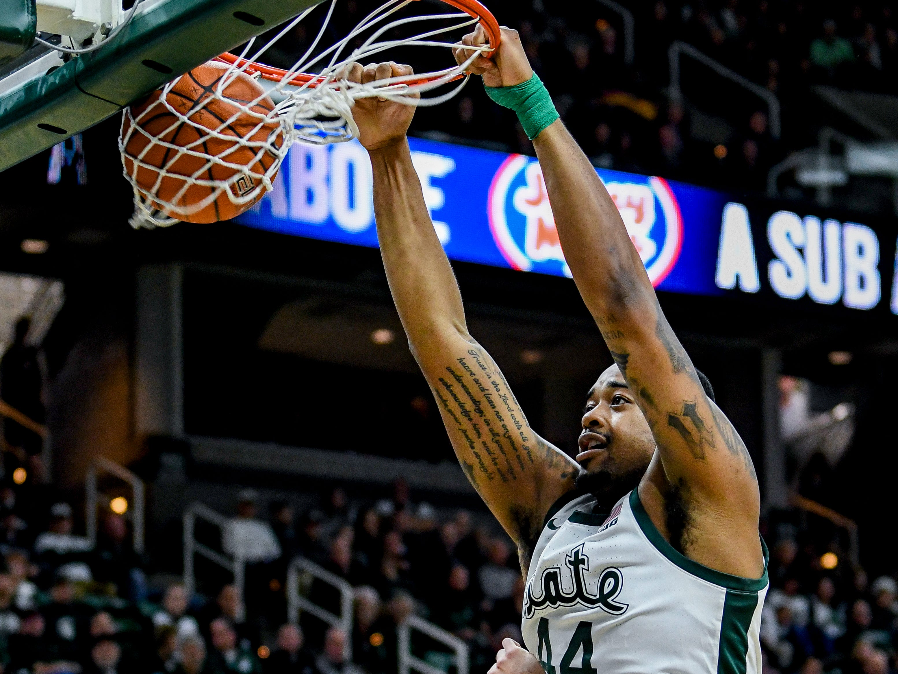 Michigan State's Nick Ward, right, dunks over Iowa's Luka Garza during the second half on Monday, Dec. 3, 2018, at the Breslin Center in East Lansing. Michigan State beat Iowa 90-68.