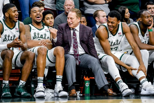 Tom Izzo, center, jokes with players, from left, Aaron Henry, Nick Ward and Xavier Tillman during the second half on Monday at the Breslin Center.