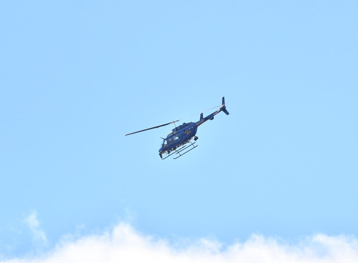 A Michigan State Police helicopter flies over the downtown Lansing U.S. Post Office, where MSP bomb squad is investigating a suspicious package.