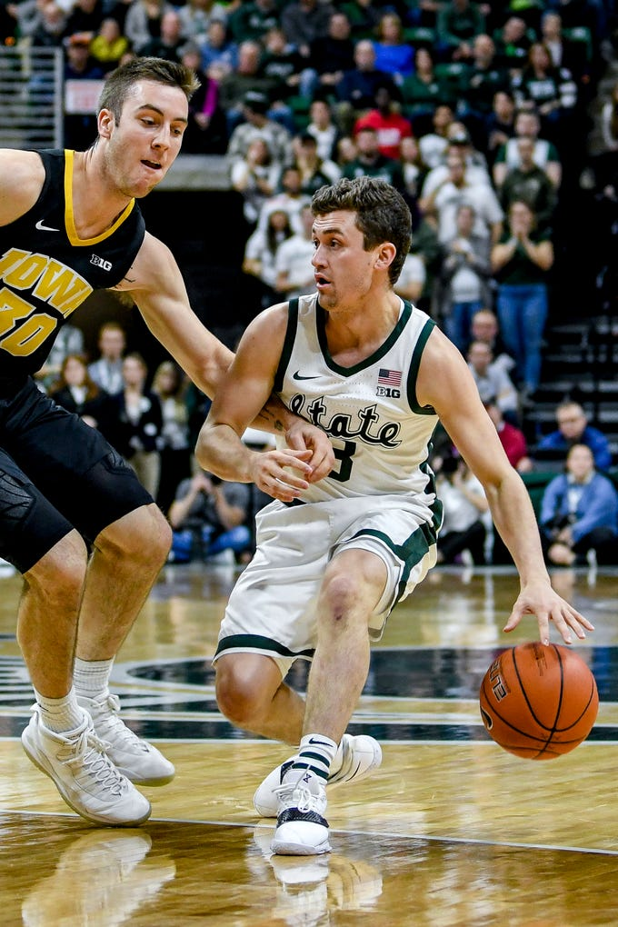 Michigan State's Foster Loyer, right, moves past Iowa's Connor McCaffery during the second half on Monday, Dec. 3, 2018, at the Breslin Center in East Lansing. Michigan State beat Iowa 90-68.