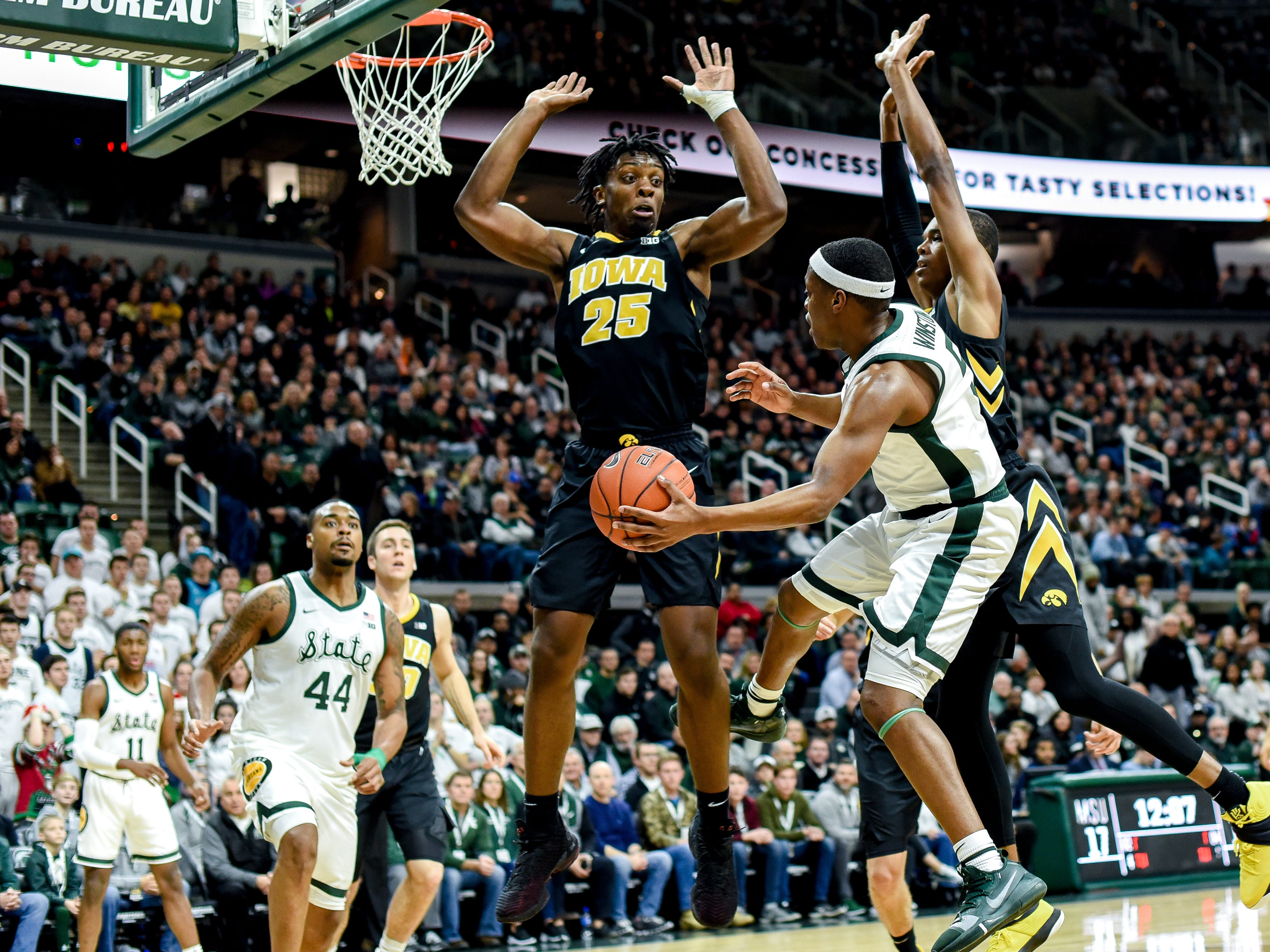 Michigan State's Cassius Winston passes to Nick Ward as Iowa's Tyler Cook, left, and Maishe Dailey defend Dec. 3, 2018, at the Breslin Center in East Lansing.