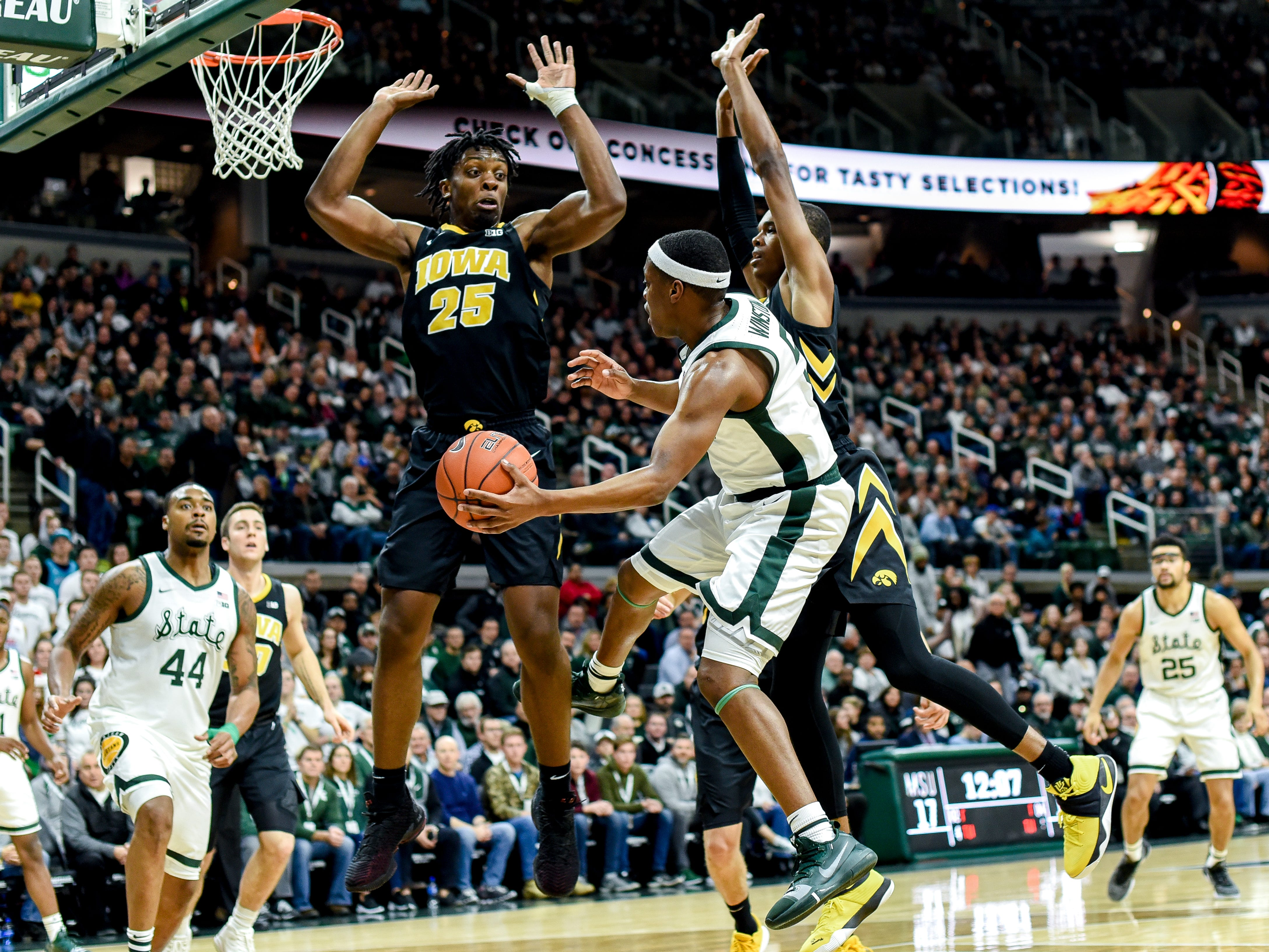 Michigan State's Cassius Winston, center, passes the ball to Nick Ward as Iowa's Tyler Cook, left, and Maishe Dailey during the first half on Monday, Dec. 3, 2018, at the Breslin Center in East Lansing.