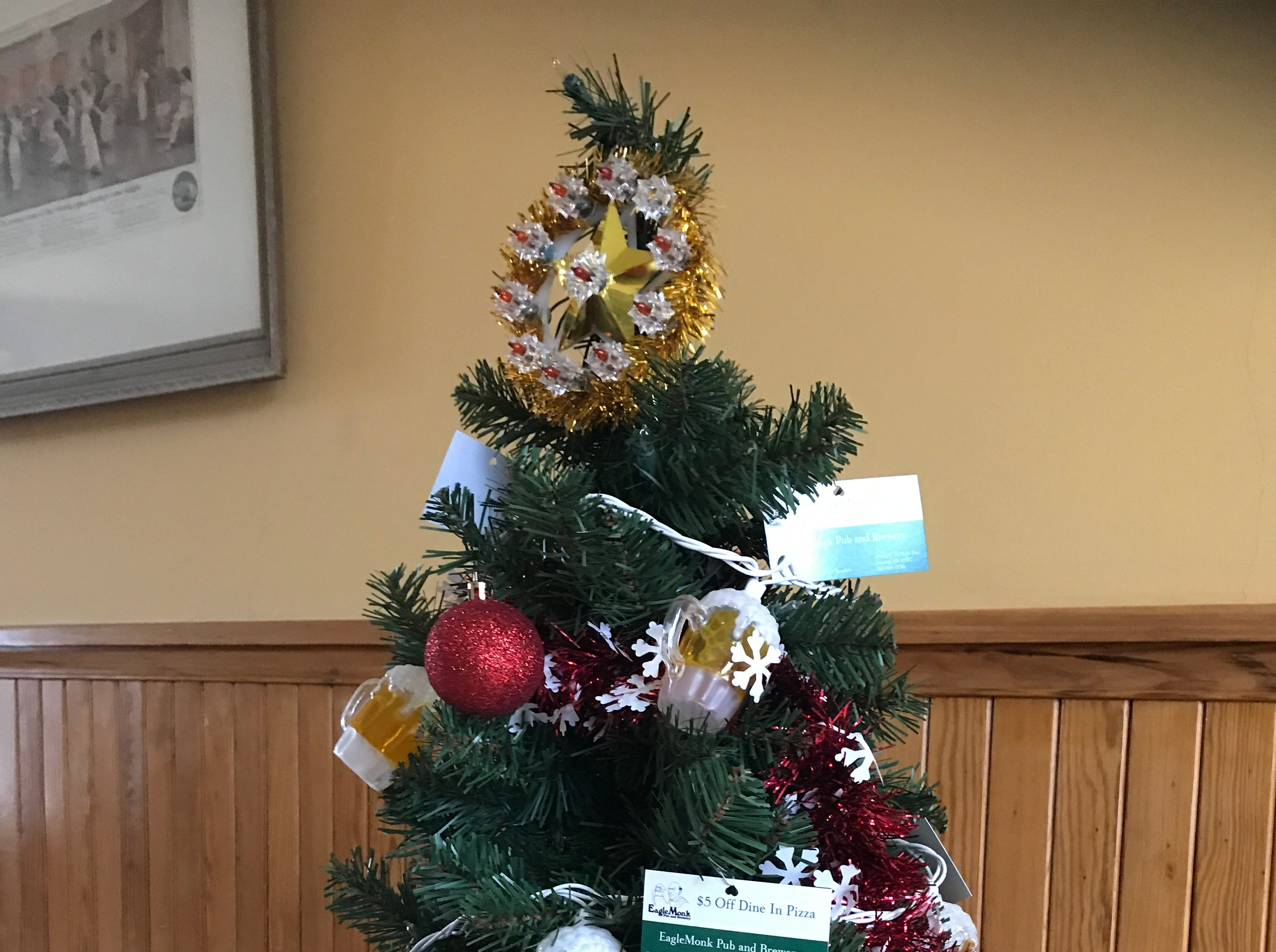 A tree is decorated with mugs of beer and coupons for Eagle Monk Pub and Brewery.
