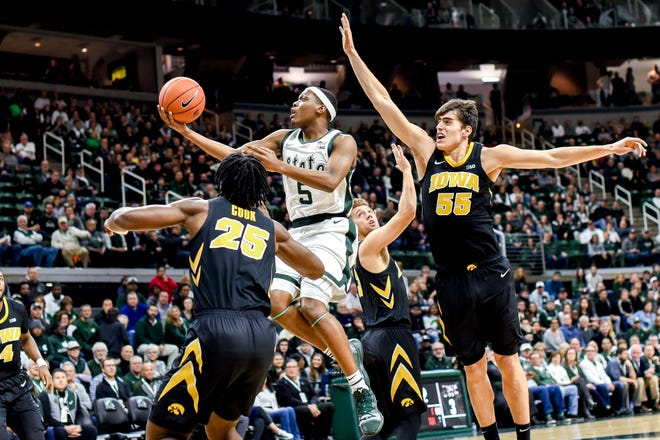 Cassius Winston, center, and MSU take on Big Ten-leading scorer Luka Garza, right, and the Hawkeyes on Tuesday night at Breslin Center.