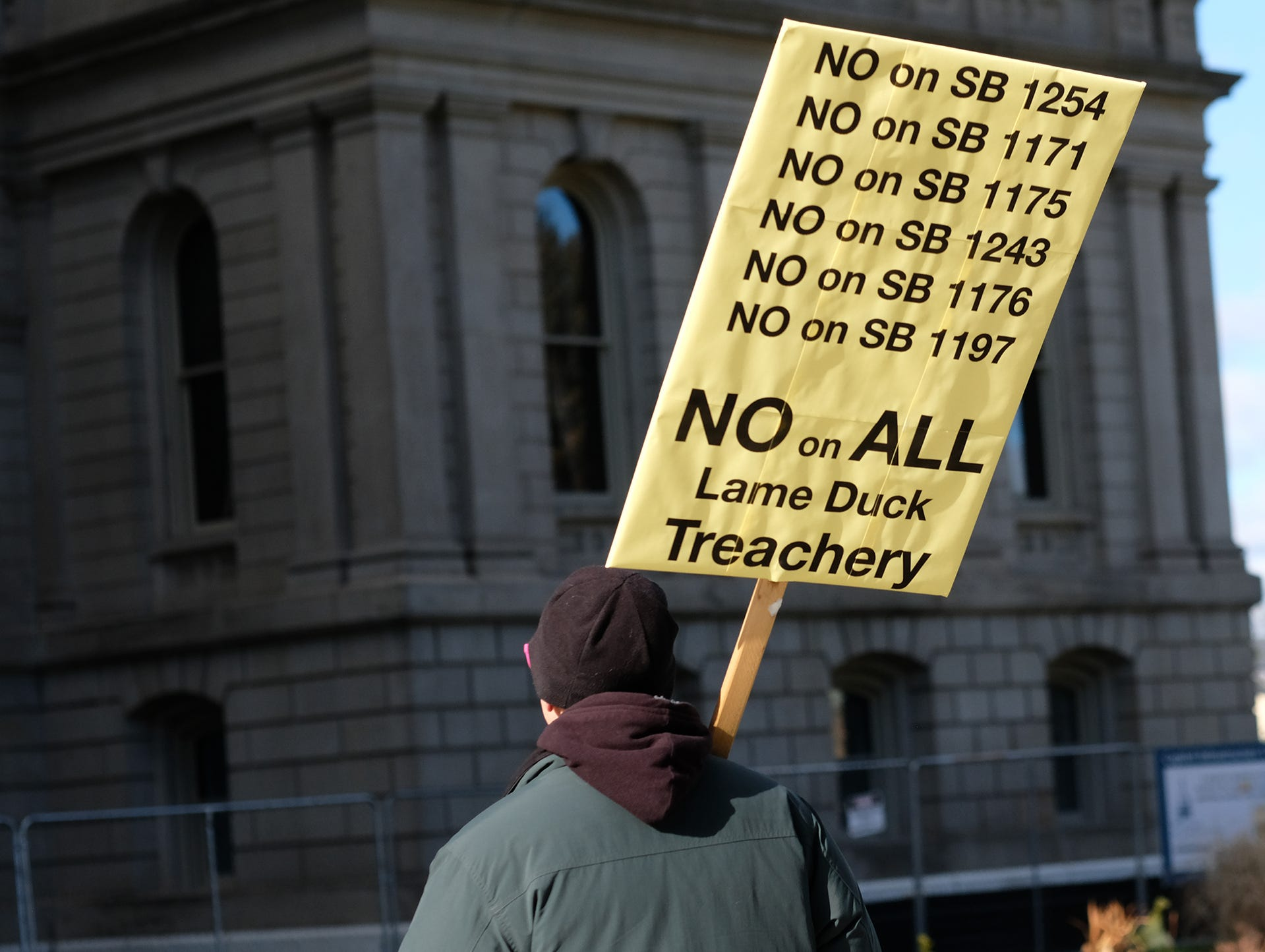 A man with a sign walks in front of the state Capitol protesting the lame duck legislation being proposed by Republicans Tuesday, Dec. 4, 2018.
