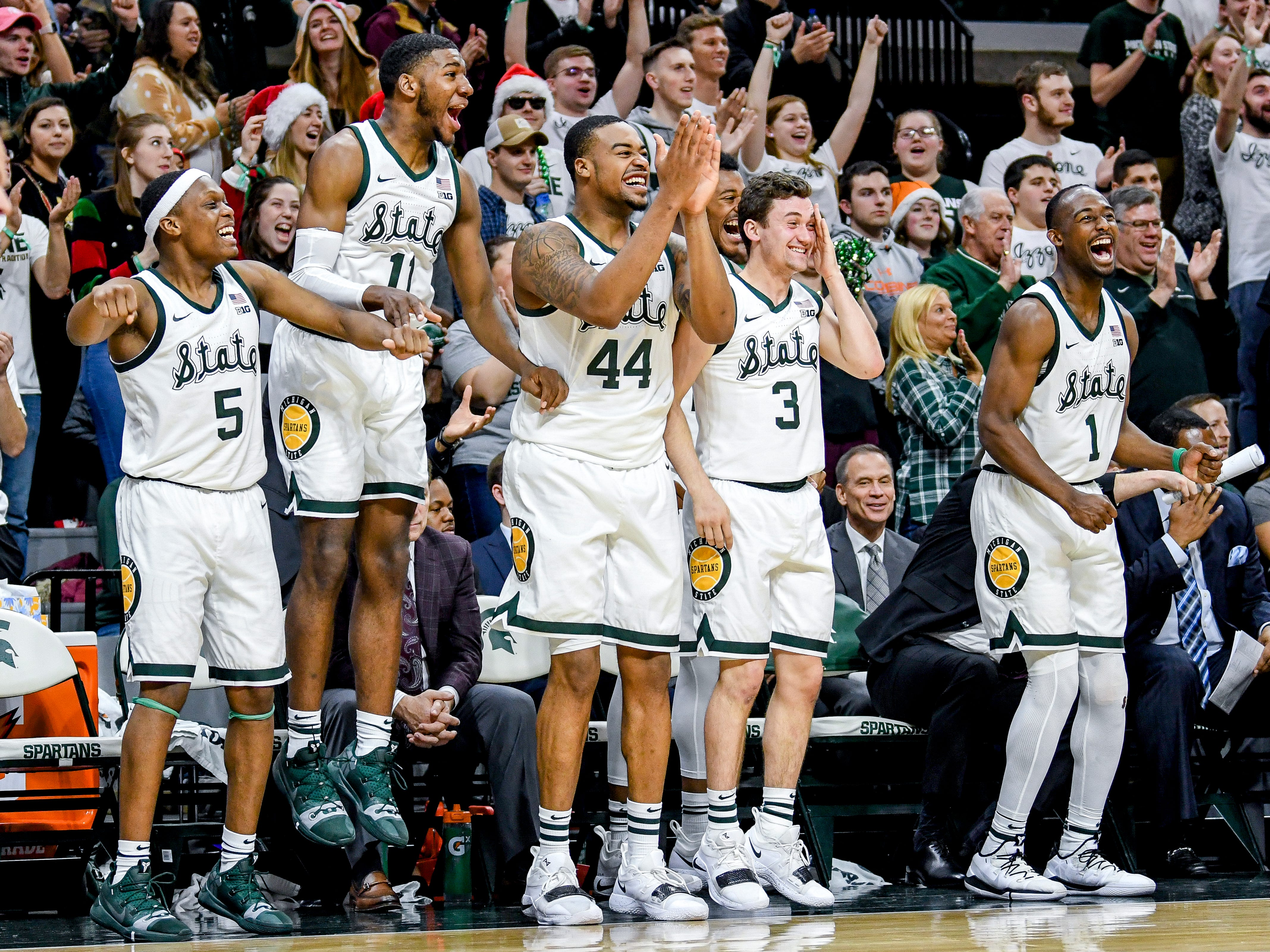 The Michigan State bench celebrates after a score late during the second half on Monday, Dec. 3, 2018, at the Breslin Center in East Lansing. Michigan State beat Iowa 90-68.
