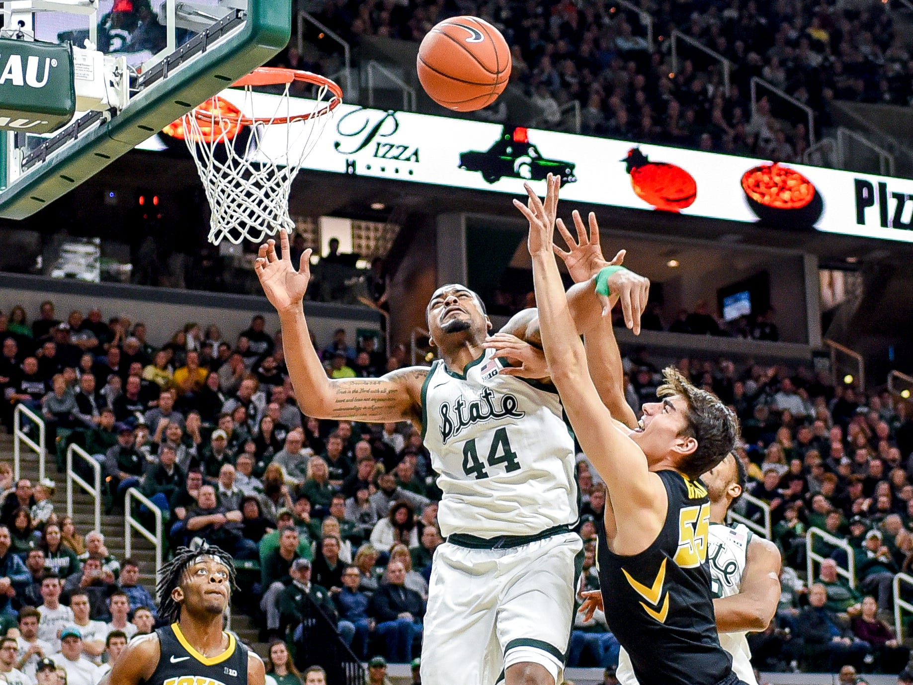 Michigan State's Nick Ward, center, blocks a shot by Iowa's Luka Garza during the second half on Monday, Dec. 3, 2018, at the Breslin Center in East Lansing. Michigan State beat Iowa 90-68.