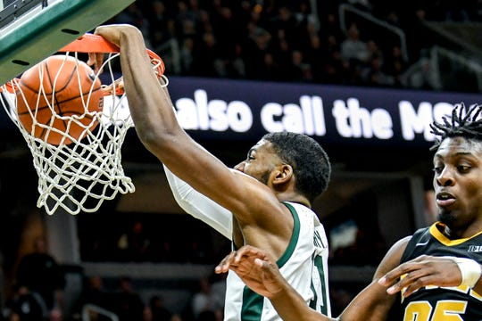 Michigan State's Aaron Henry dunks as Iowa's Tyler Cook defends during the first half on Monday, Dec. 3, 2018, at the Breslin Center in East Lansing.