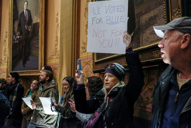 Ursula Averill from Lansing, chants as she protests the lame duck legislation inside the state Capitol Tuesday, Dec. 4, 2018.