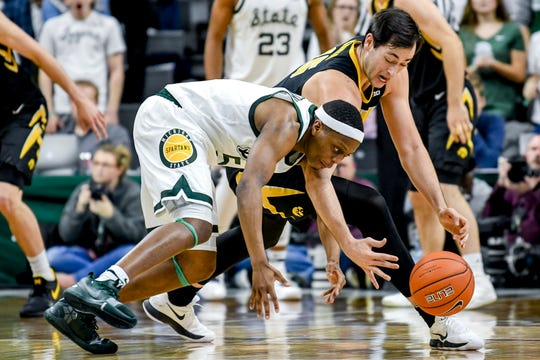 Michigan State's Cassius Winston, left, and Iowa's Ryan Kriener go after the ball in the second half Monday, December 3, 2018 at the Breslin Center in East Lansing. Michigan State beat Iowa 90-68.