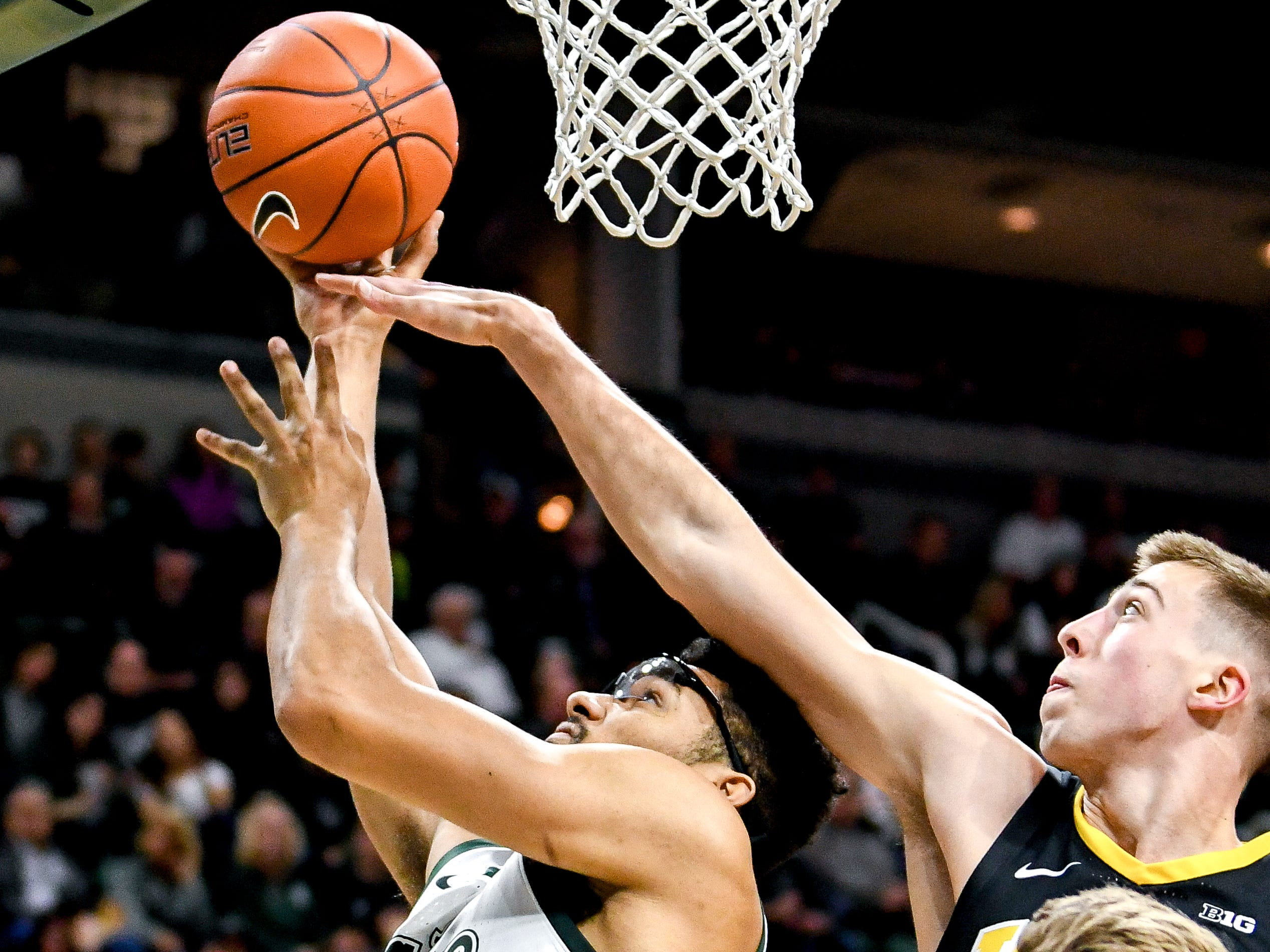 Michigan State's Kenny Goins, left, scores as Iowa's Joe Wieskamp defends during the first half on Monday, Dec. 3, 2018, at the Breslin Center in East Lansing.