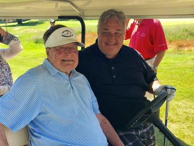 Michael Patrick Shiels poses with former president George H.W. Bush while golfing.