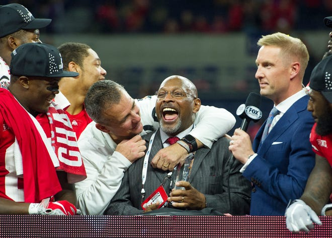 Ohio State football coach Urban Meyer gives Buckeyes legend Archie Griffin a playful hug as Griffin prepares to present the Big Ten Championship Game MVP trophy that bears his name to quarterback Dwayne Haskins (not pictured) after the Buckeyes' 45-24 victory over Northwestern.
