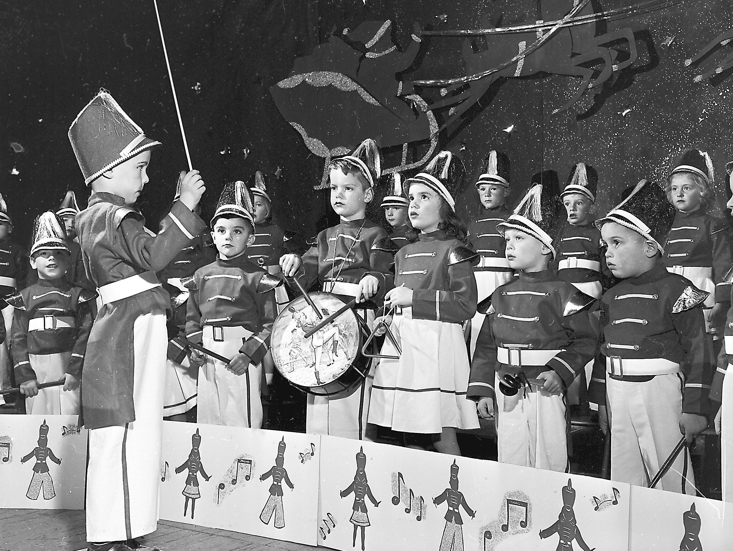 Young musicians of Holy Child Kindergarten, under the baton of Pat Mooney, greeted the Yule season with a series of lively tunes on 21 Dec 1953 during a program of song and pageantry at the Little Theatre in Memphis Museum.
