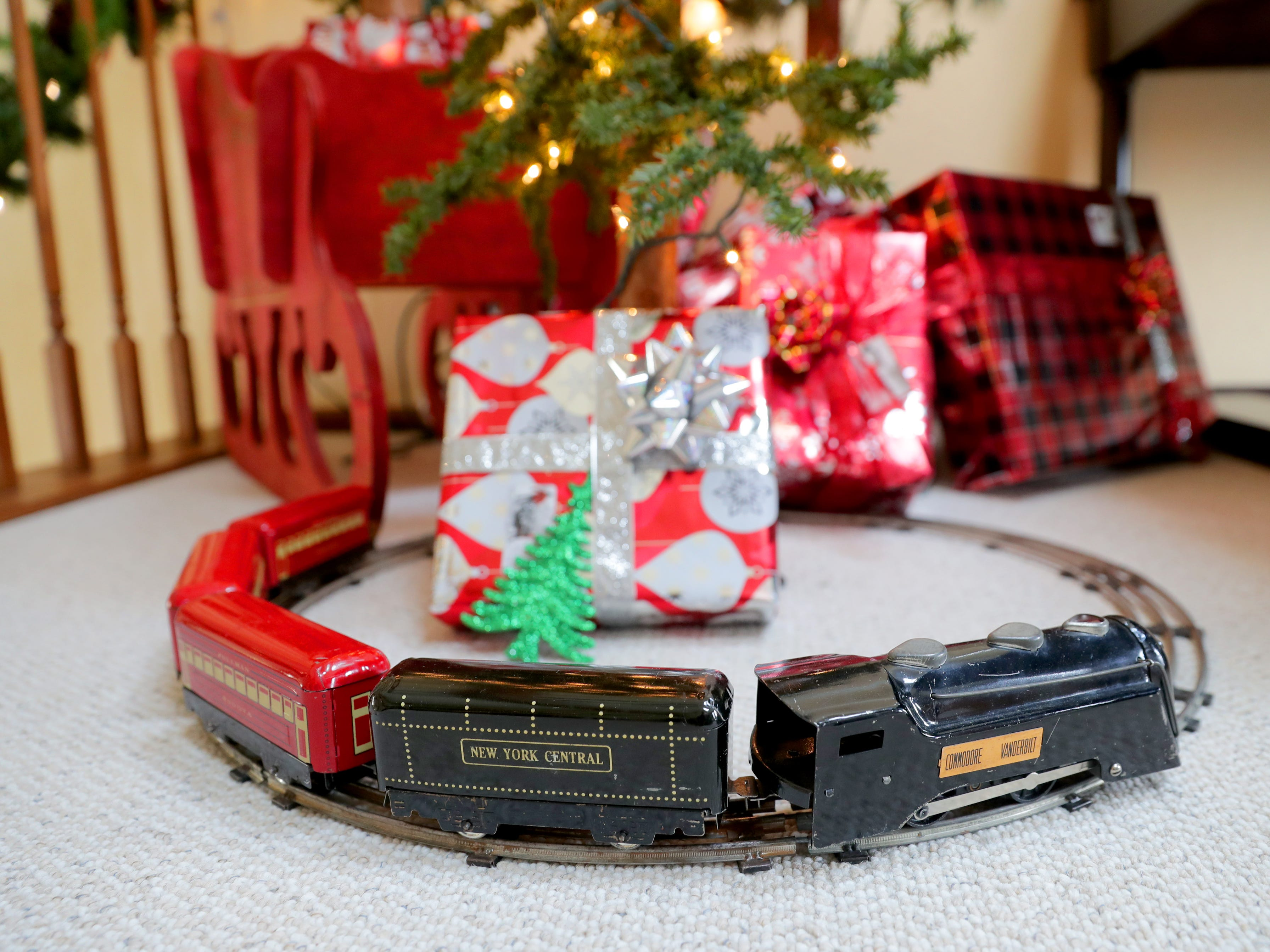An antique model train from the 1950s surrounds a tree in the office.