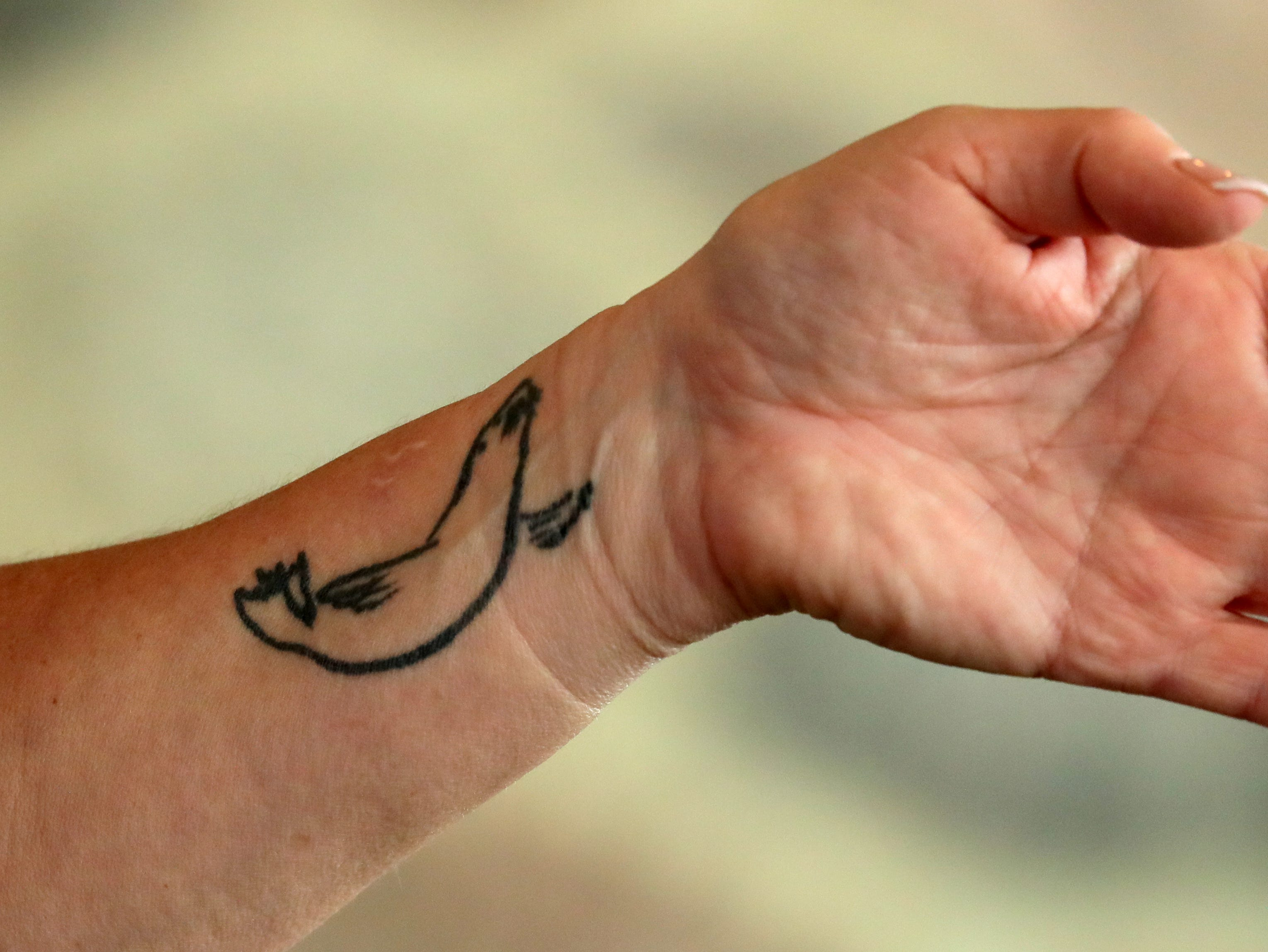 Shelley Ballmann, president of Oceans of Fun, shows her sea lion tattoo.
