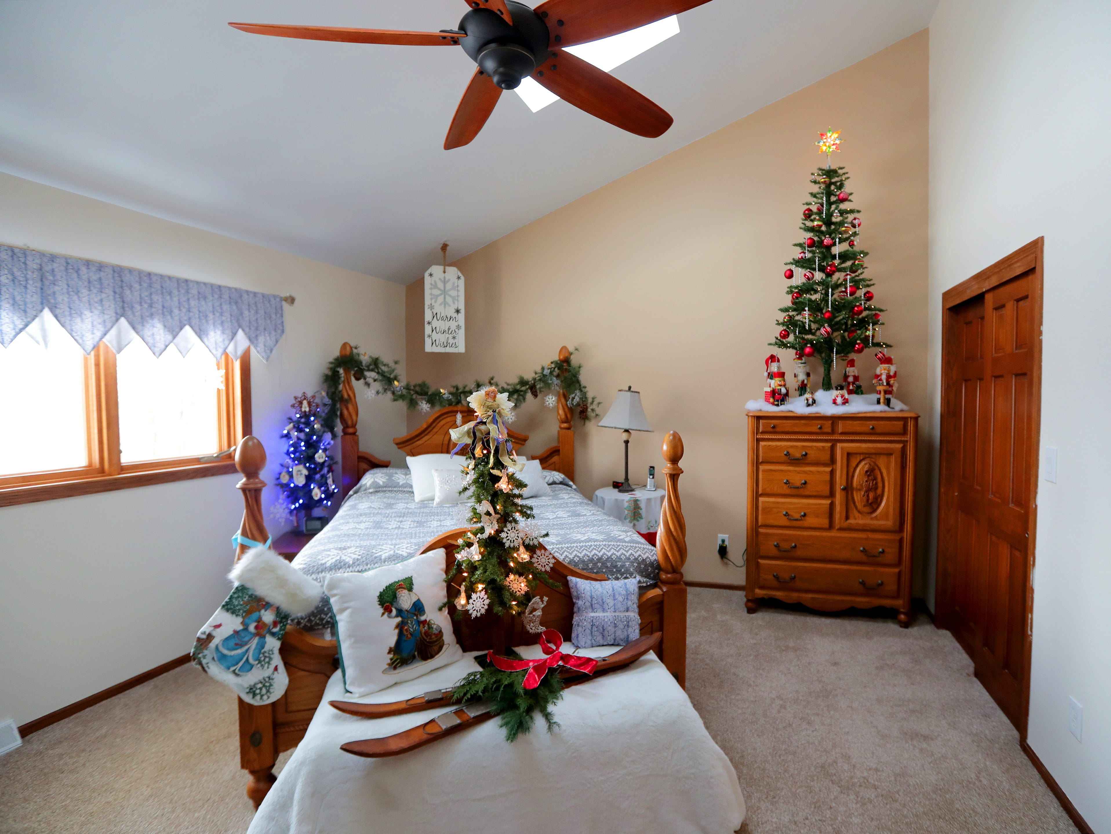 The master bedroom on the second floor is decked out in holiday decorations, including three small trees.