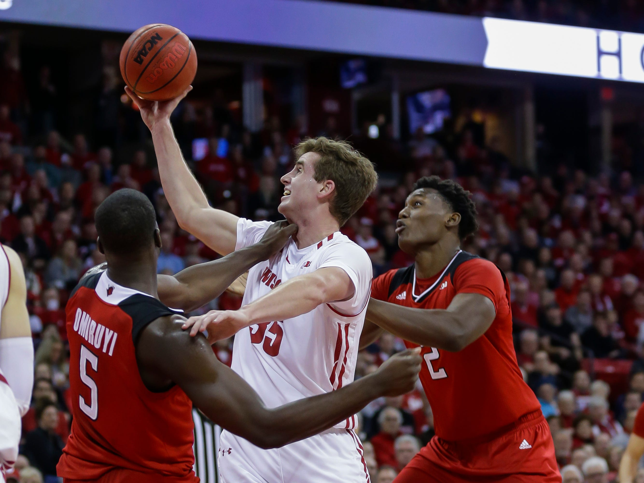 Wisconsin forward Nate Reuvers goes up for a shot between Eugene Omoruyi (5) and Shaquille Doorson of Rutgers during the first half on Monday night.