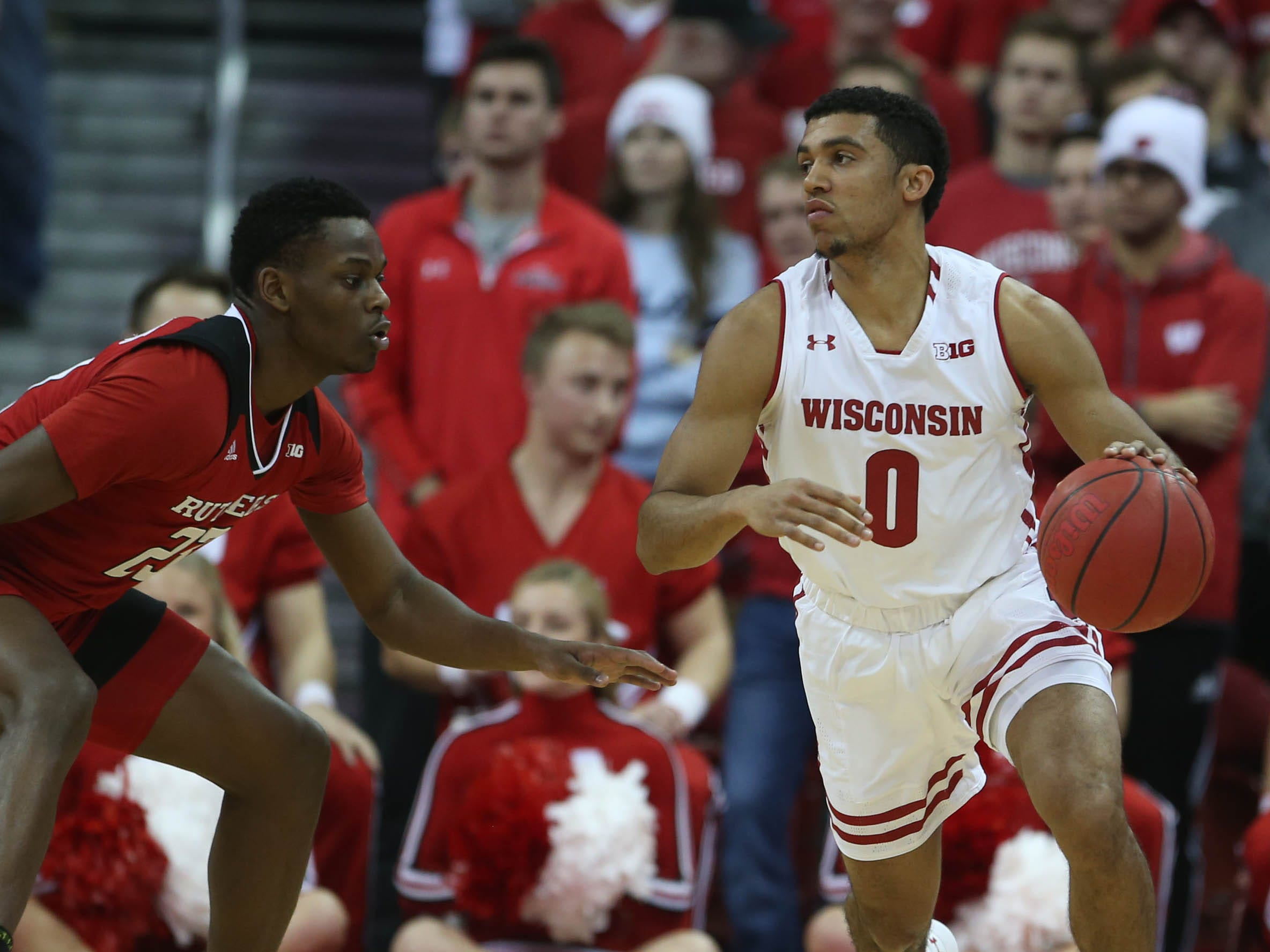 Wisconsin point guard D'Mitrik Trice scans the court as he dribbles against Rutgers guard Montez Mathis during the first half.