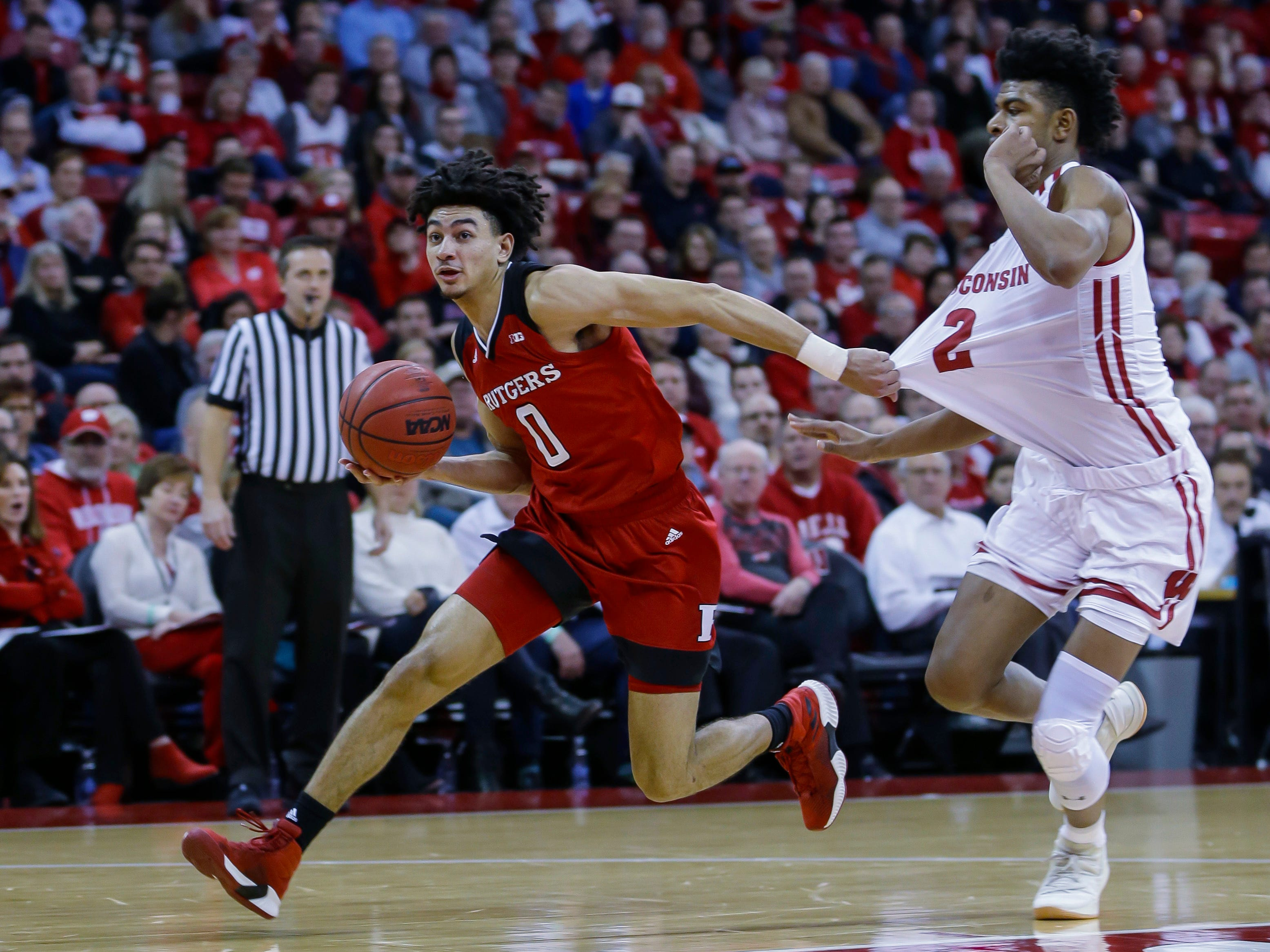 Geo Baker of Rutgers is whistled for a foul as he grabs a hold of Wisconsin forward Aleem Ford's jersey during the first half on Monday night.