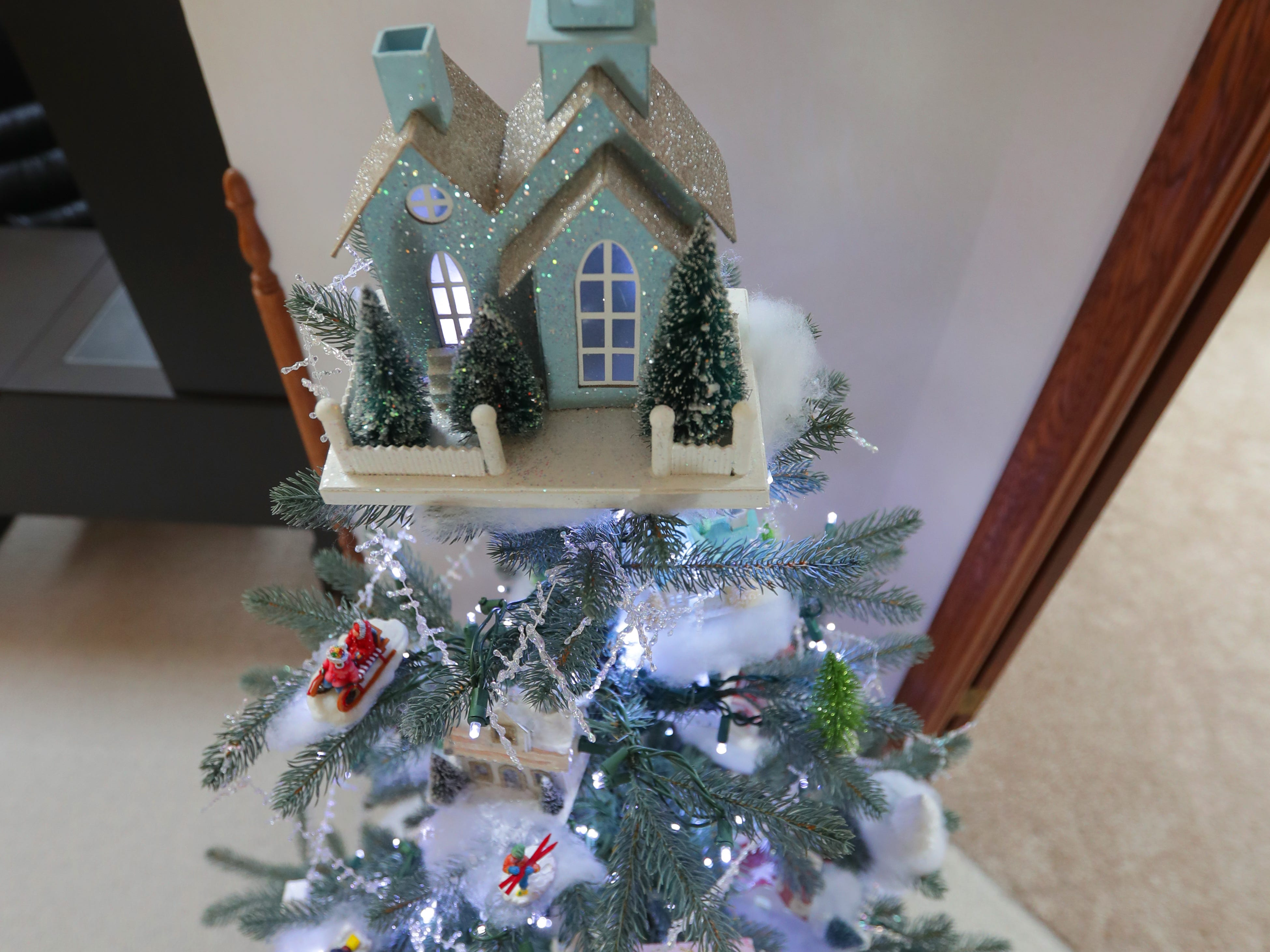 A tree on the upper floor is decorated with miniature Christmas village houses.