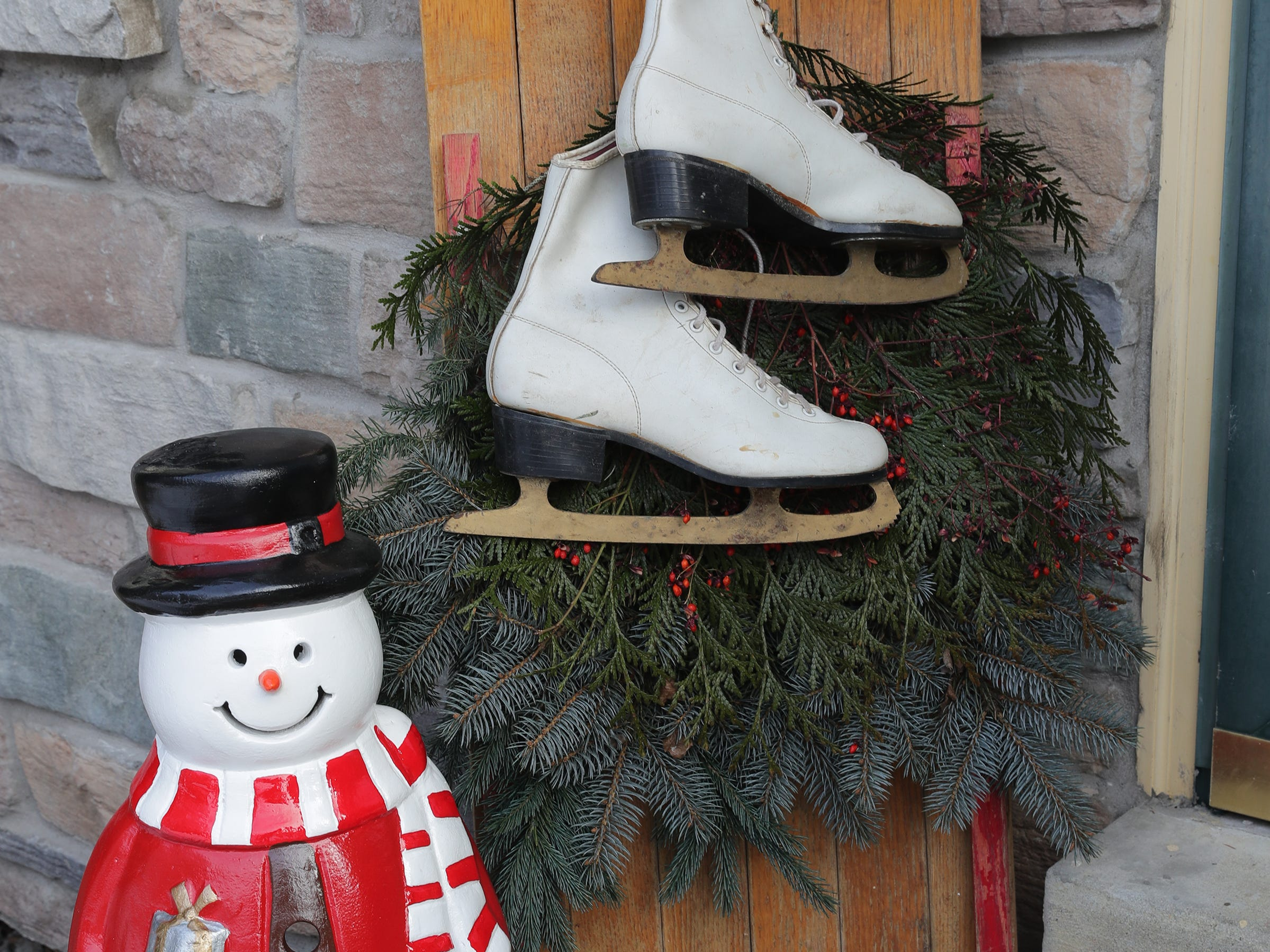 A snowman and old pair of ice skates hanging on a sled greet visitors to the Muskego home.