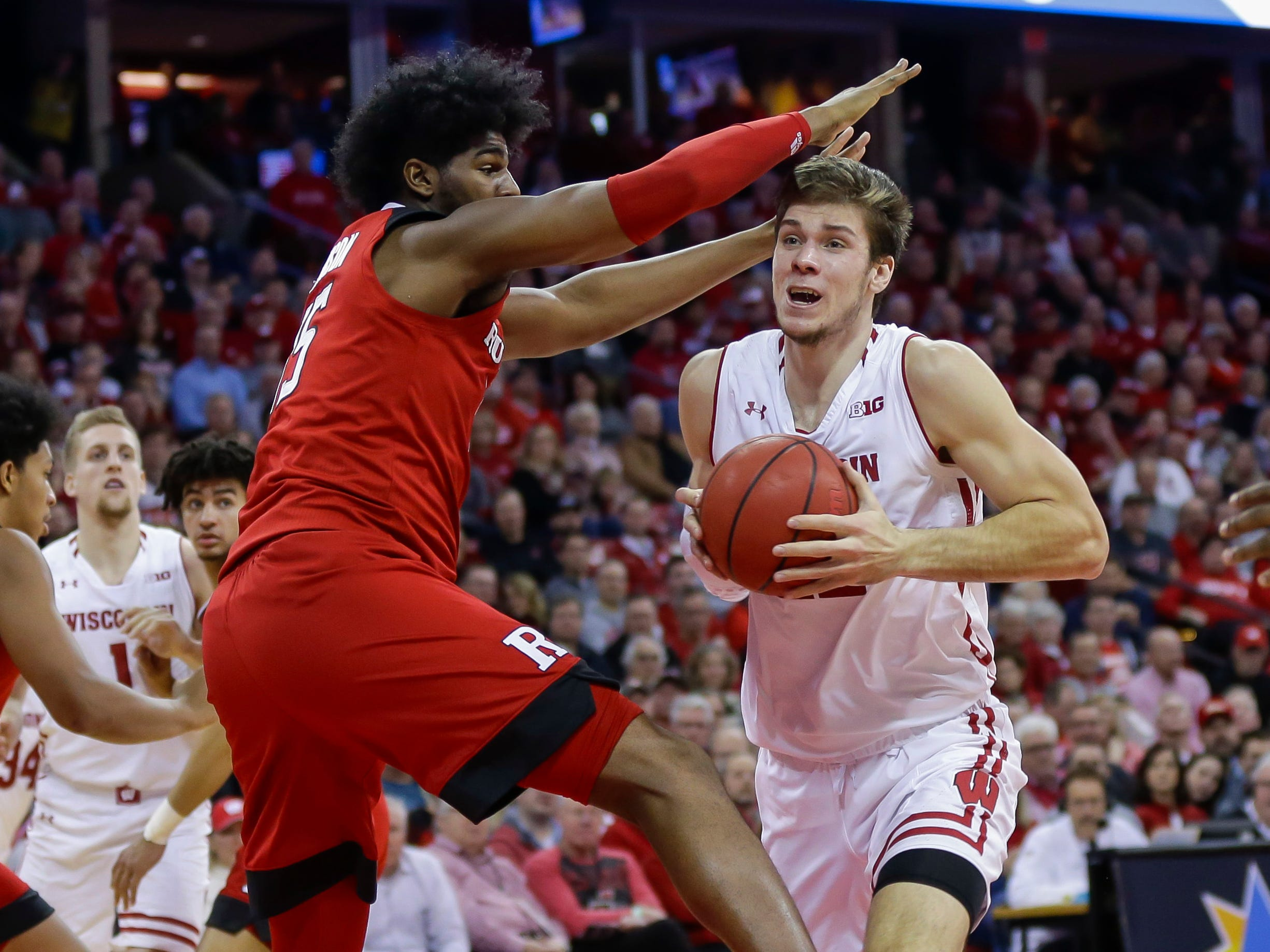 Wisconsin forward Ethan Happ gets past Myles Johnson of Rutgers on a drive after getting him up in air during the second half on Monday.