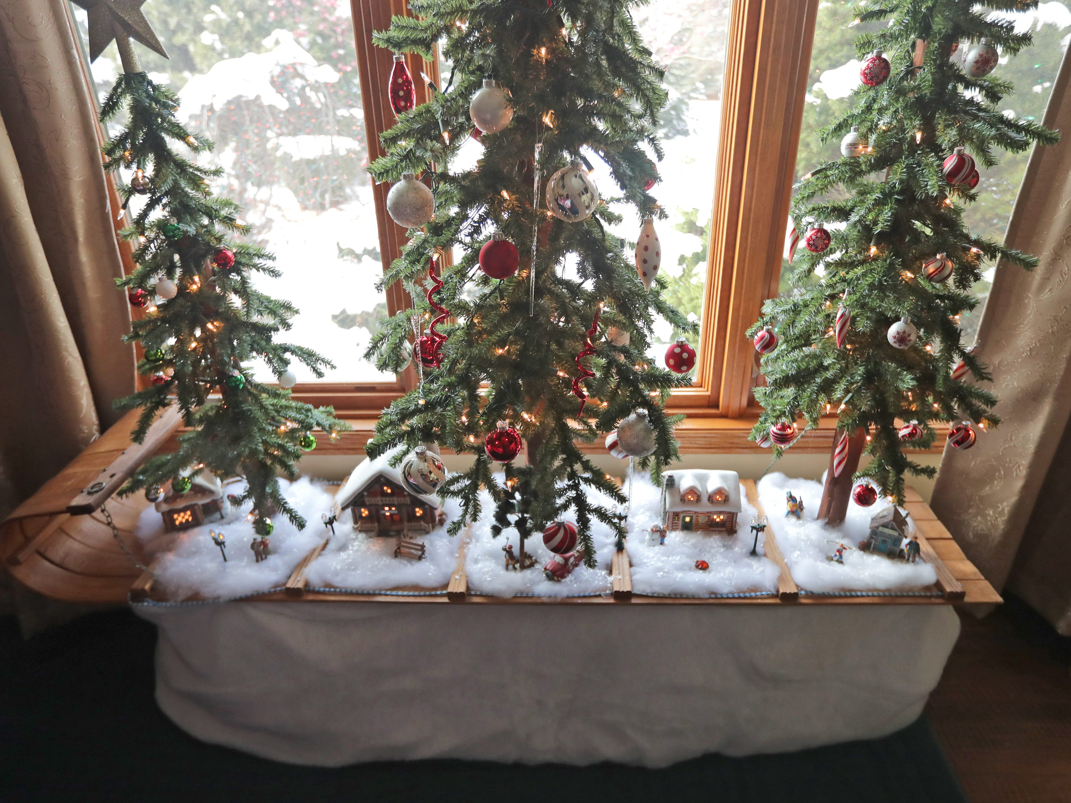 Smaller trees and a Christmas village are displayed on an old toboggan in the guest bedroom on the first floor.