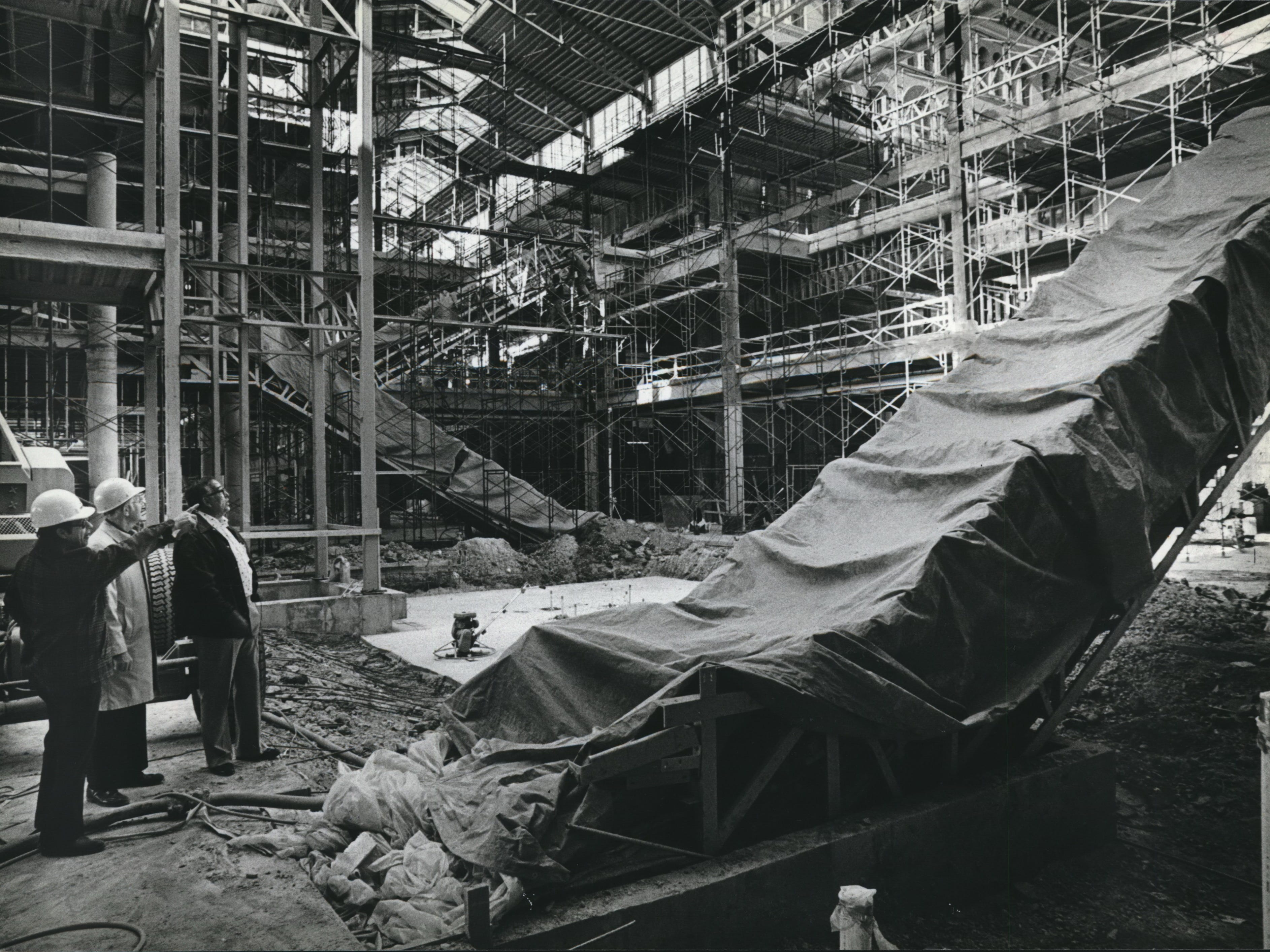 The Grand Avenue Mall Viewing progress in the atrium of the three-story central court were (from left) John Shalek, electrical inspector; Wally Koepp, an electrical engineer with Staff Electric Co., and Emil Rukavina, elevator inspector. The Milwaukee city inspectors and Koepp stood near an escalator (foreground) that will take shoppers to the second level in an area that used to be 3rd St.The new shopping mall is scheduled to open late in July, 1982. Milwaukee- Downtown- Redevelopment Program.
