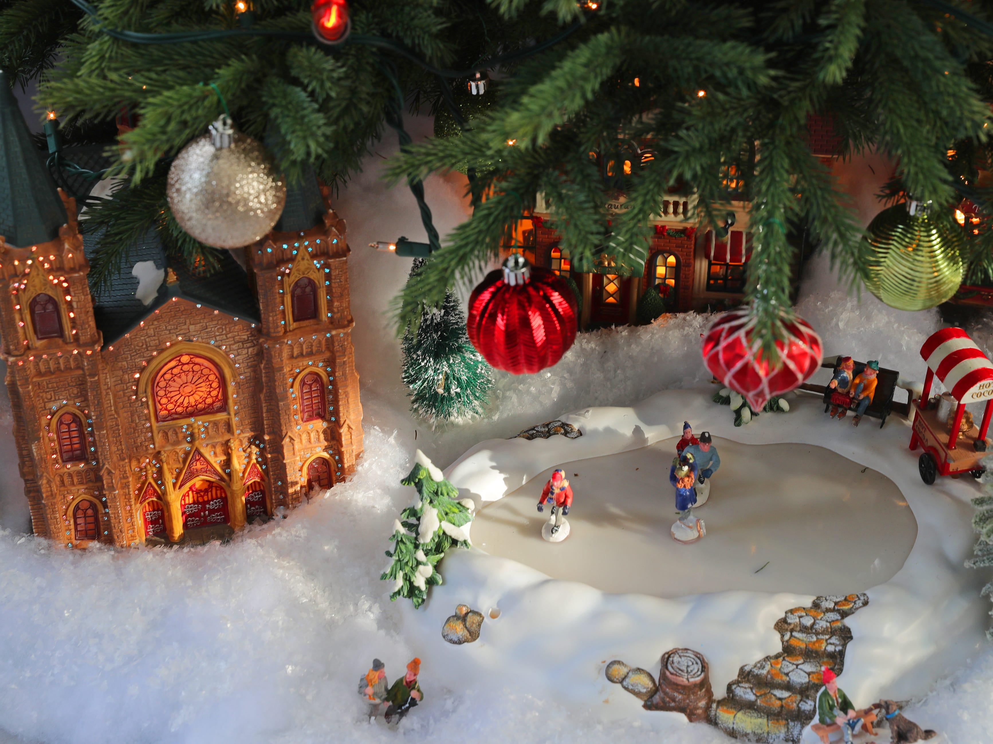 The lone real Christmas tree, inside the three-season room, has a Christmas village underneath with a miniature ice skating pond.