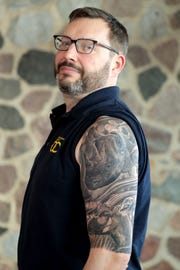 Ray Hren, a pachyderm keeper, shows his rhinoceros tattoo over a tattoo of a bongo antelope.
