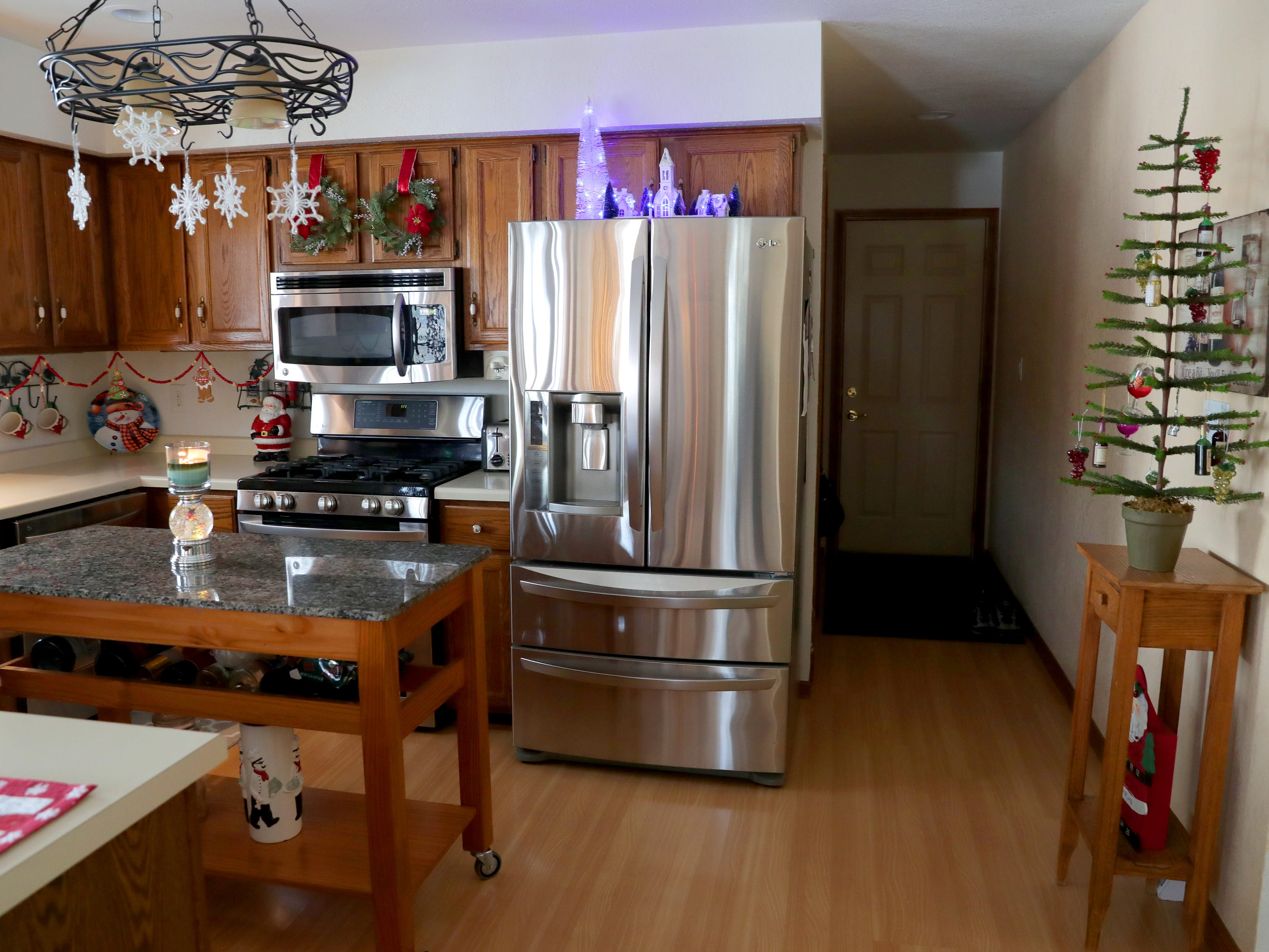The kitchen showcases various holiday decorations, including snowflakes hanging from the chandelier.