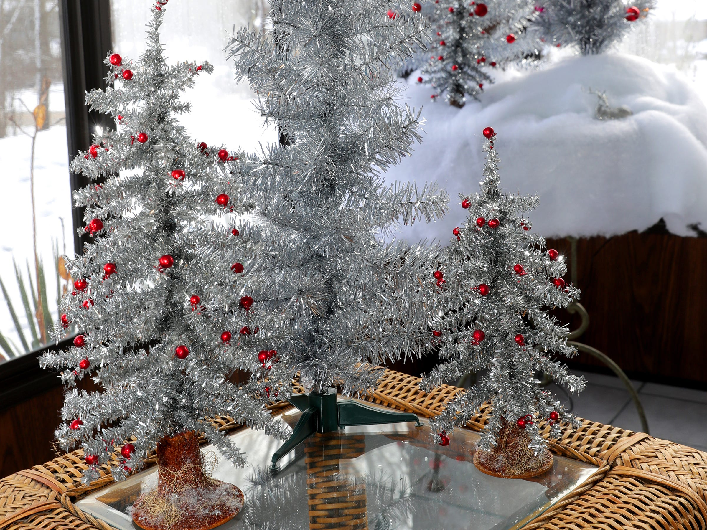 An assortment of aluminum tabletop trees with tiny red ornaments spruce up the three-season room.