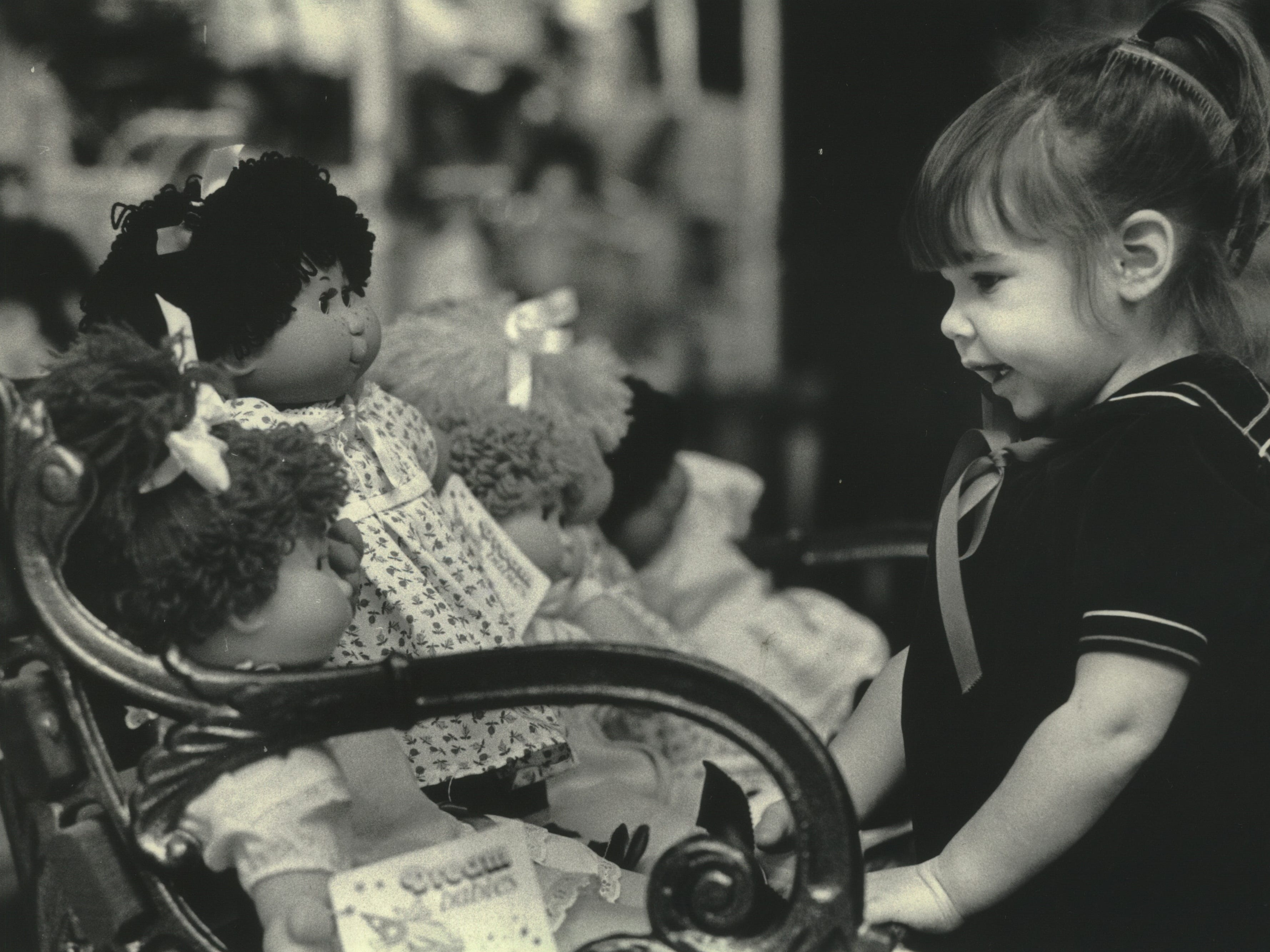 """Victoria Fleischer, 2, looked at Dream Babies in the Hello Doll """"E"""" shop at the Grand Avenue retail center. Shoppers"""
