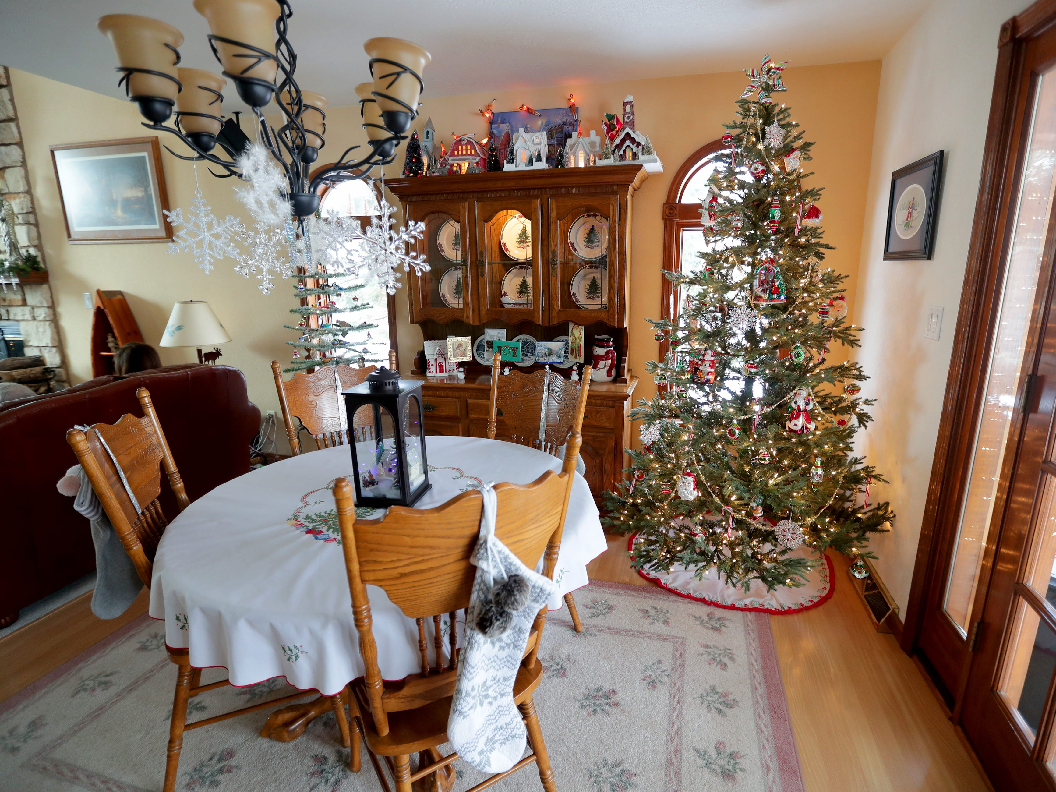 The dining room off the kitchen includes another tree and Christmas plates displayed in the china hutch.